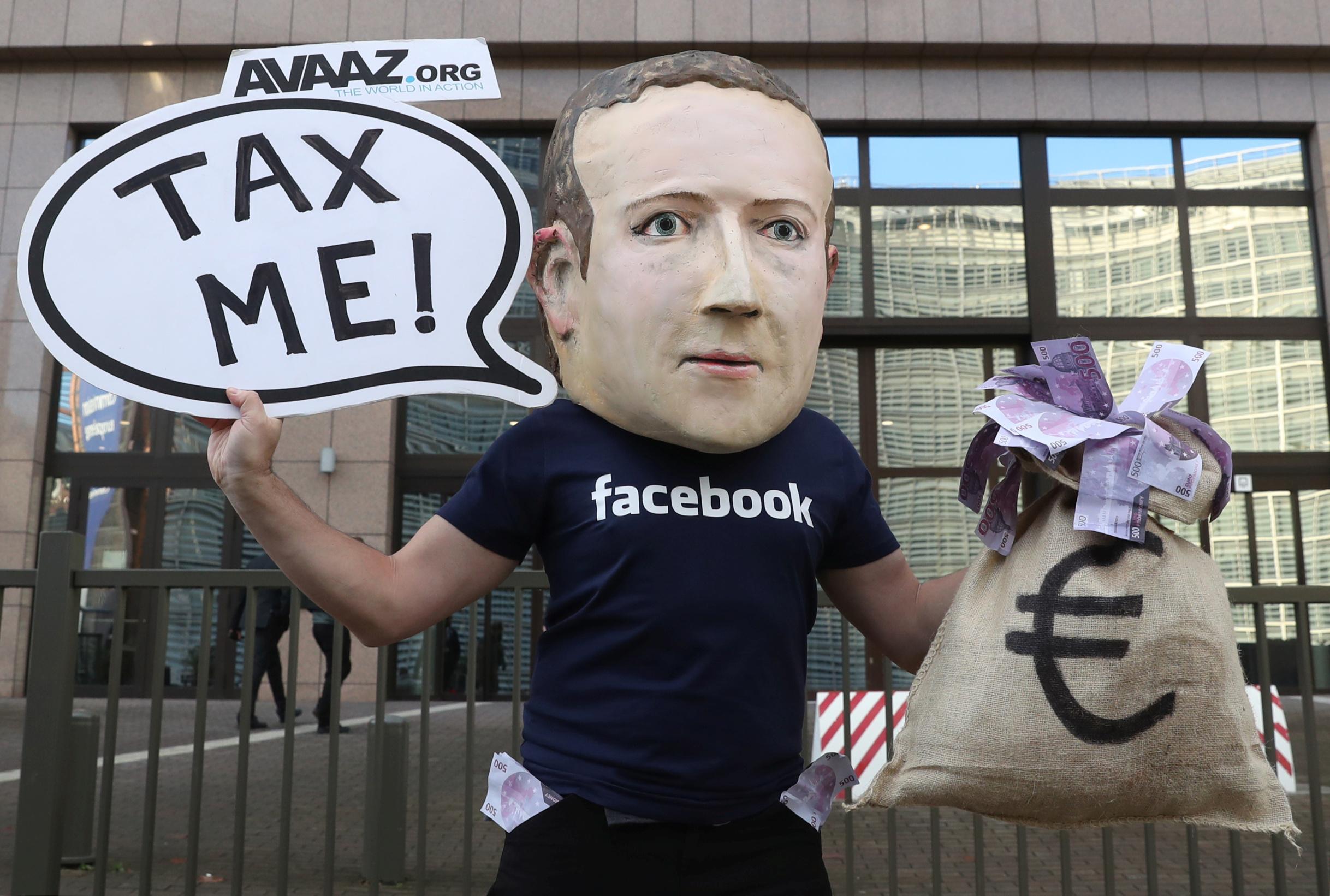 Aktivist prosvjeduje za uvođenje poreza na digitalne tvrtke s maskom Marka Zuckerberga