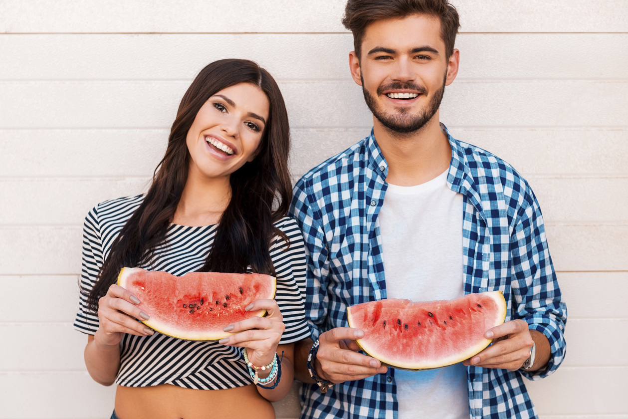 Sweet and juicy like their love. Cheerful young loving couple holding slices of watermelon and looking at camera while standing outdoors togehter
