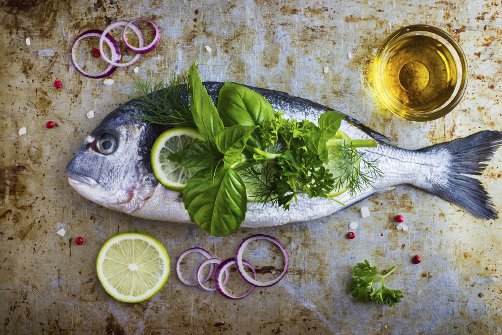 fresh raw dorado fish with spicy herbs, top view