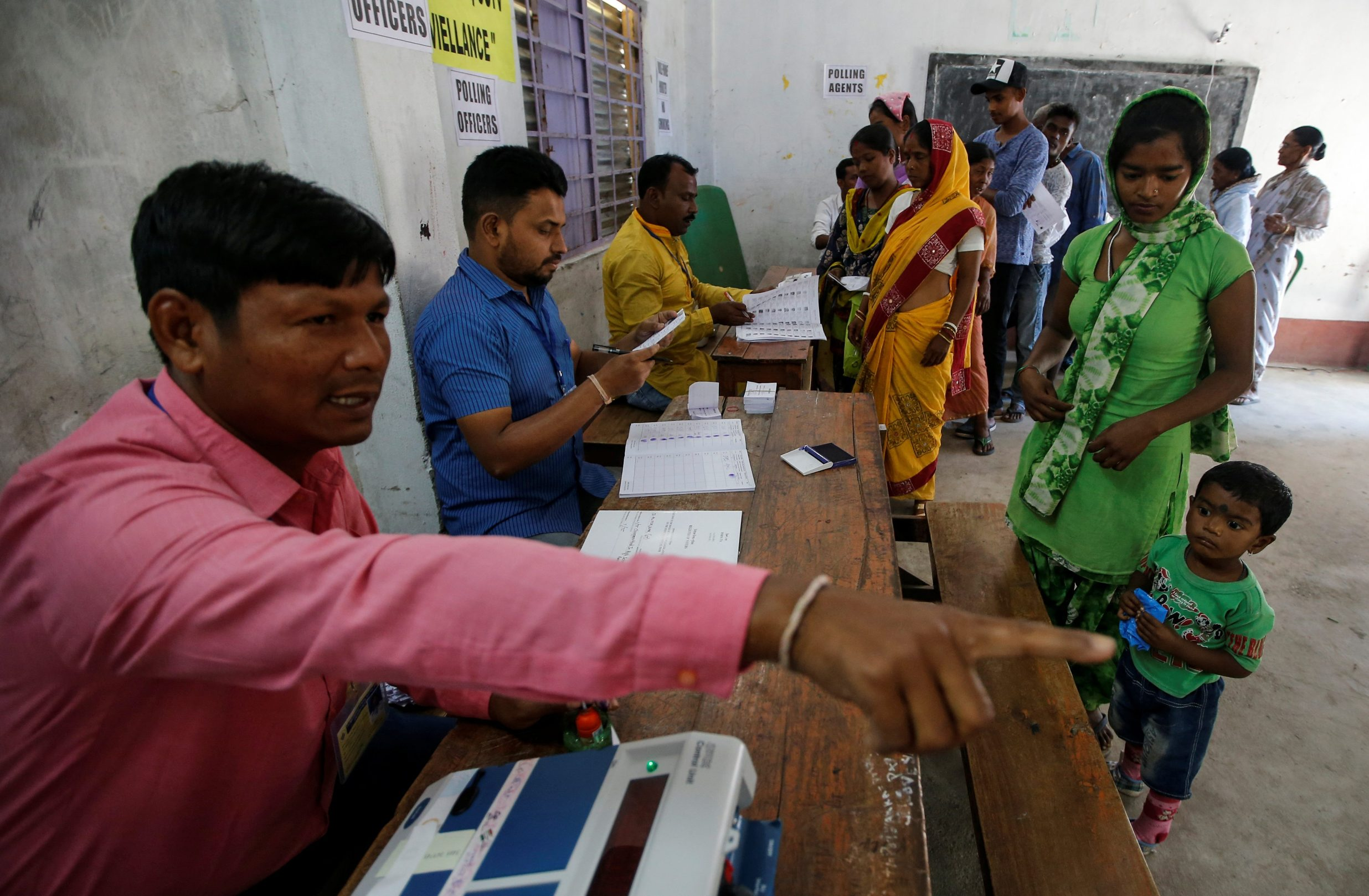 An election official guides a woman as she arrives to vote at a polling station during the first phase of general election in Alipurduar district, in the eastern state of West Bengal, India, April 11, 2019. REUTERS/Rupak De Chowdhuri