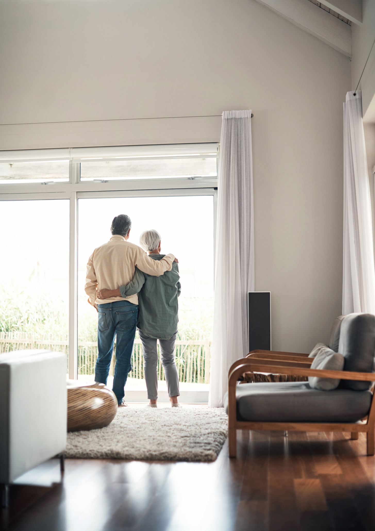 Rearview shot of an elderly couple looking out of their house together during a relaxing day at home