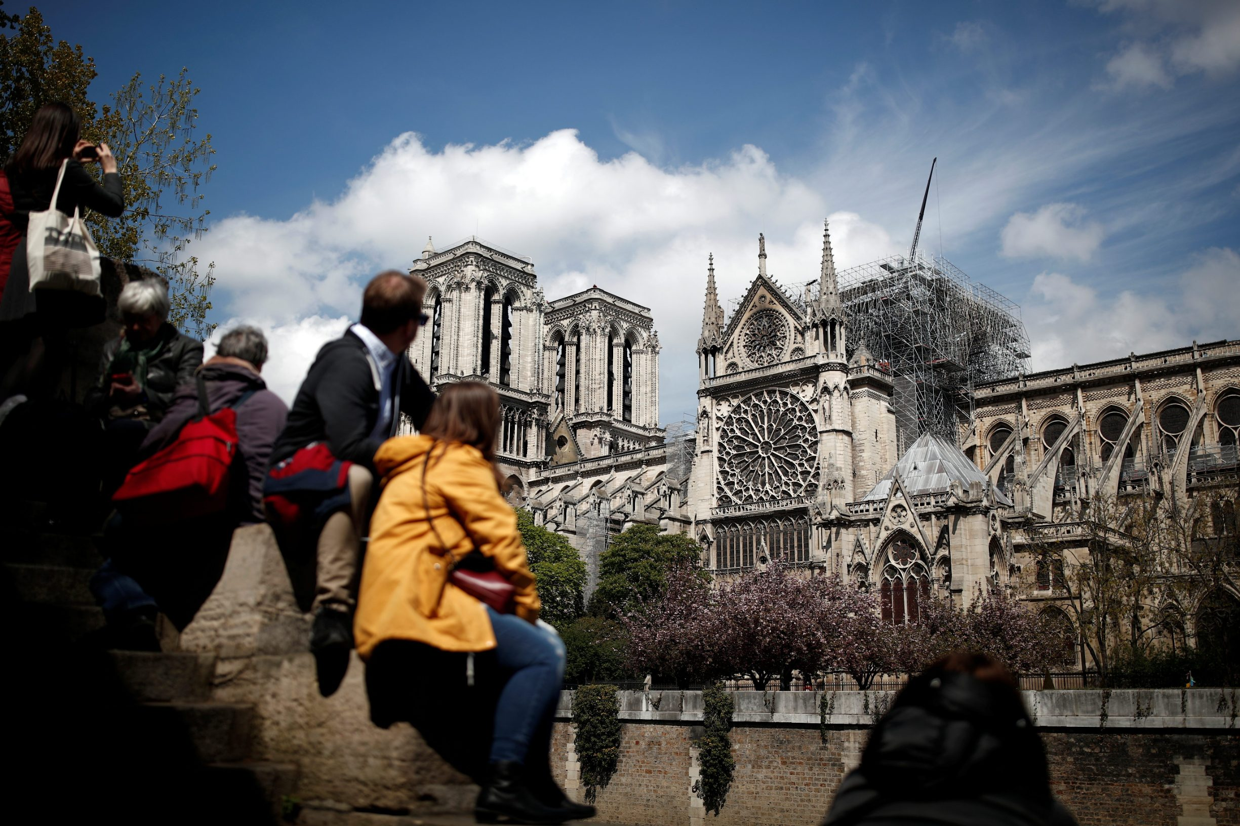 People look at Notre-Dame Cathedral two days after a massive fire devastated large parts of the gothic structure in Paris, France, April 17, 2019.   REUTERS/Benoit Tessier