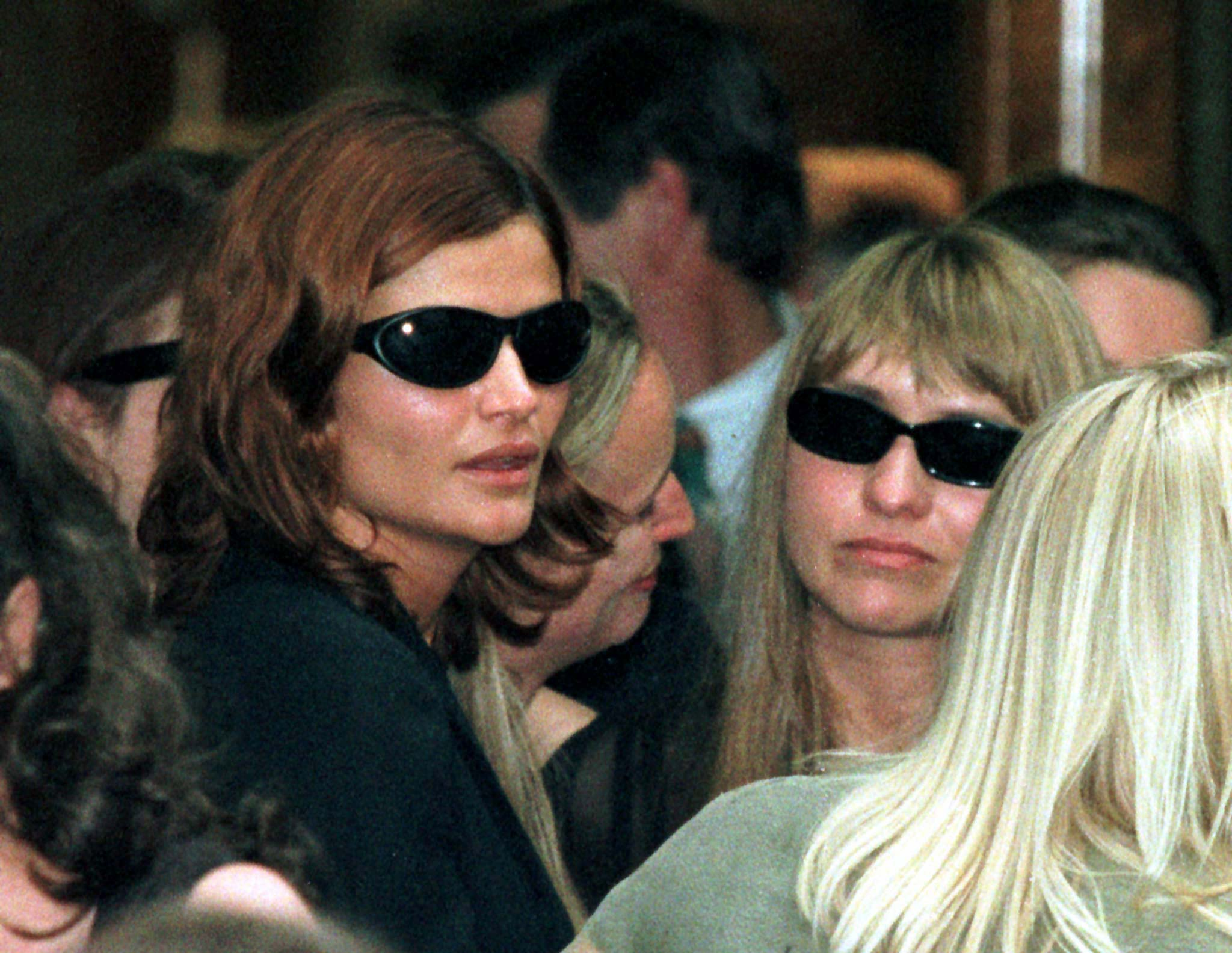 Supermodel Helena Christensen (L) is pictured with an unidentified friend after the funeral of Australian rock star Michael Hutchence at Sydney's main Anglican Church November 27. Thousands of fans watched the emotional service outside on large video screens while relatives and friends crowded inside. Hutchence was found dead in his Sydney hotel room November 22.    ? QUALITY DOCUMENT - PBEAHUMRCBA