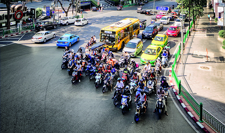 Bangkok Thailand elevated scene in Pathum Wan commercial area with central world shopping mall to the left. Commuters in cars and motor cycles are waiting at the intersection in the foreground.