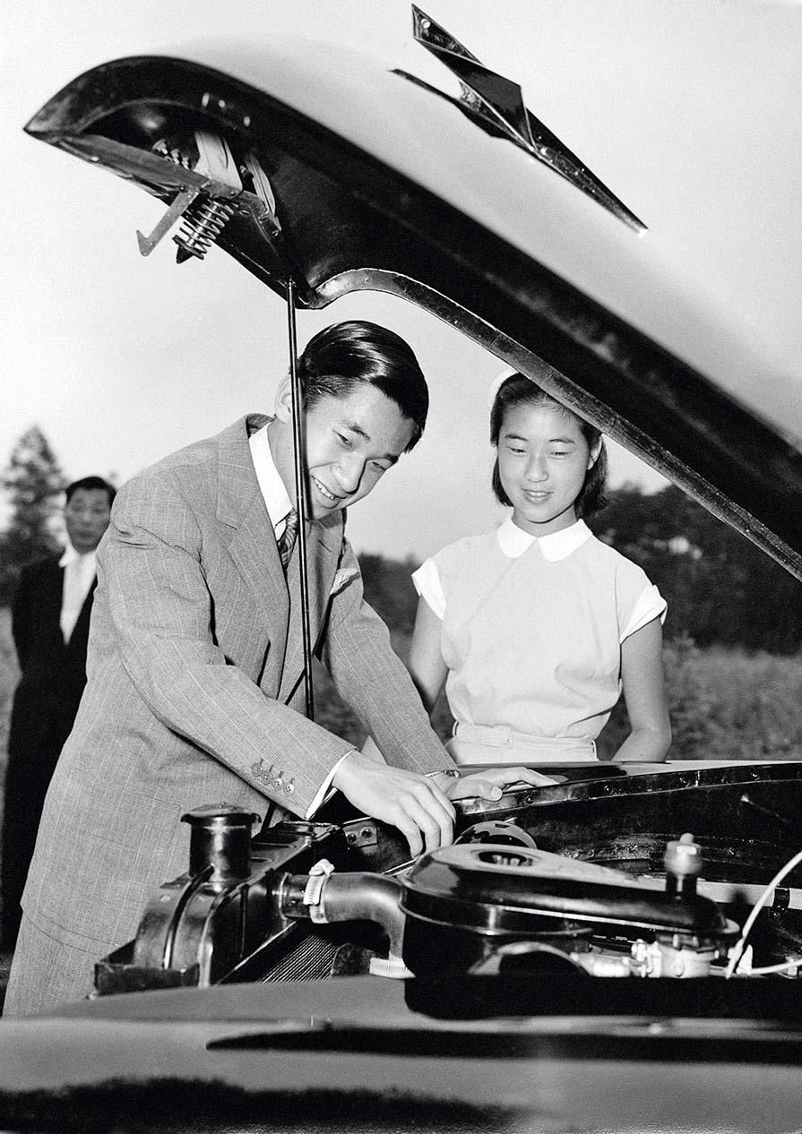 Crown Prince (later Emperor) of Japan, Akihito examining the engine of his 1954 Prince Motor Company car as his younger sister Princess Takako looks on, circa 1955. Akihito is spending the summer at Karuizawa, Nagano. (Photo by Central Press/Hulton Archive/Getty Images)