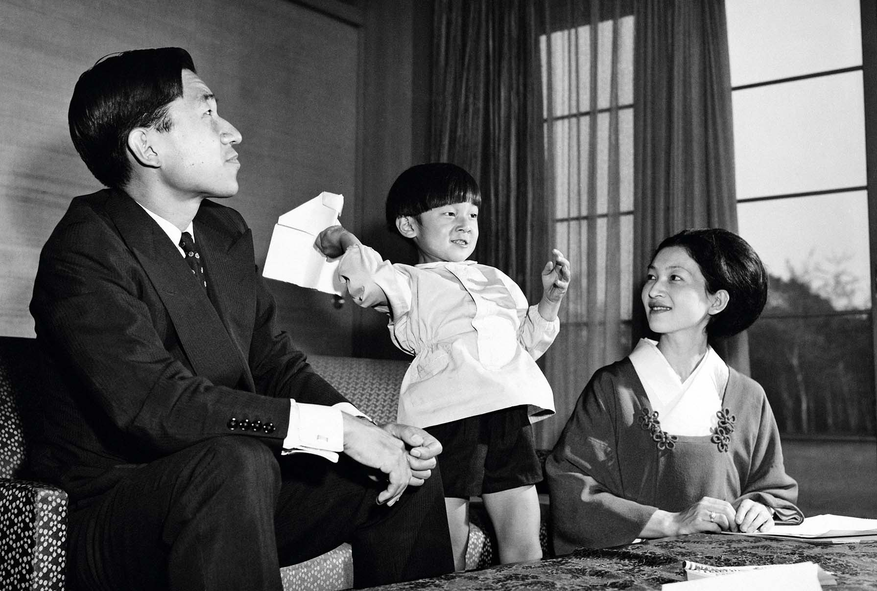 Crown Prince Akihito of Japan and Crown Princess Michiko with their son Prince Hiro, aka Crown Prince Naruhito of Japan, making paper aeroplanes on the occasion of Princess Michiko's 31st birthday, Togu Palace, Tokyo, 23rd October 1965. (Photo by Keystone/Hulton Archive/Getty Images)