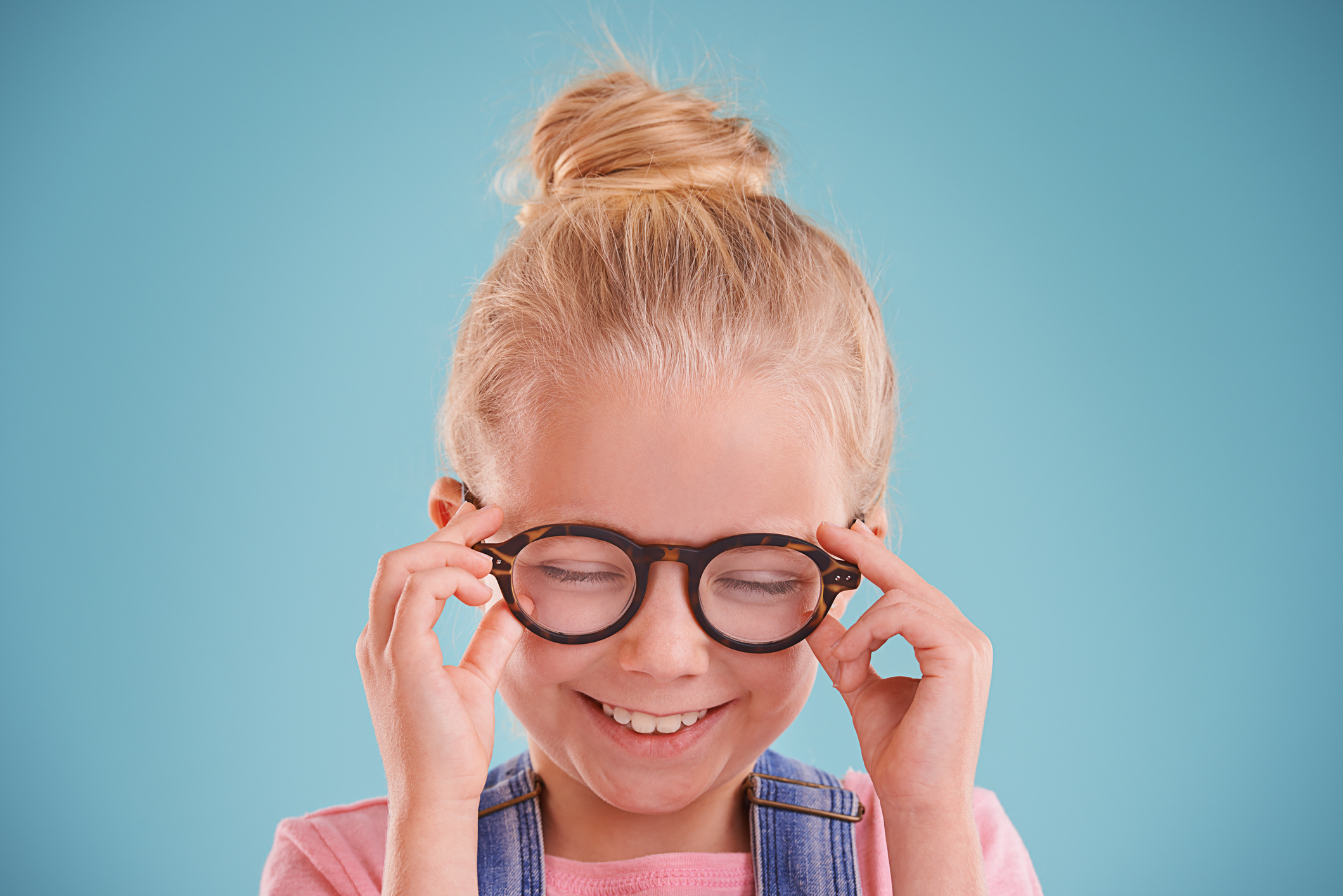 Studio shot of a little girl wearing hipster glasses on a blue background