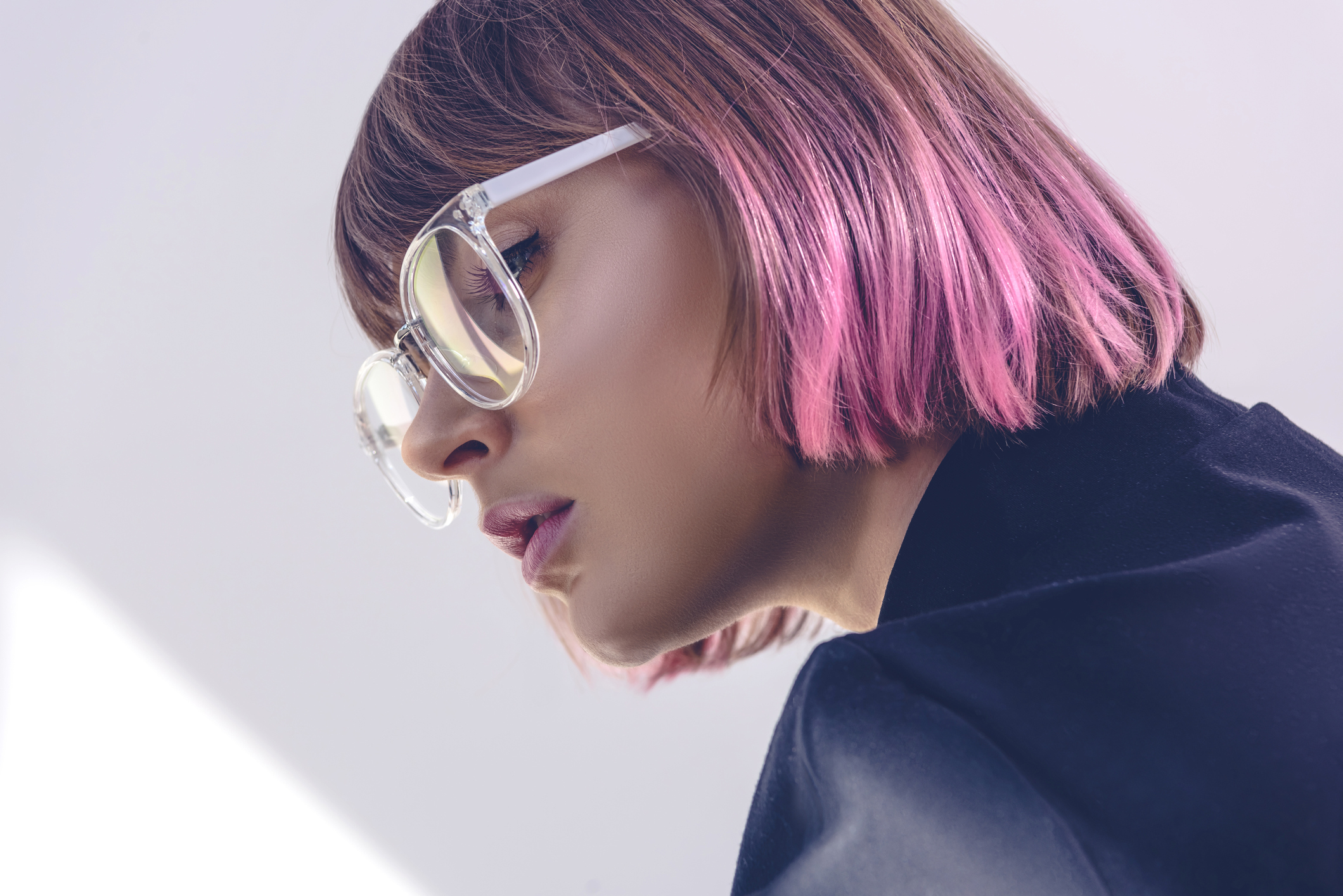 portrait of stylish girl with pink hair and glasses on white