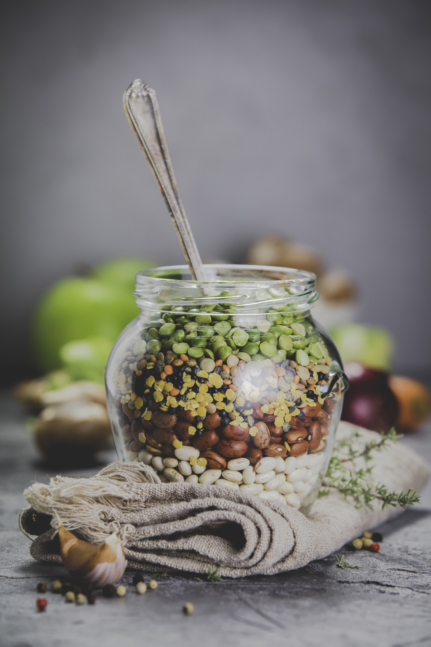 Legumes - lentils chickpeas beans green peas in a glass jar and raw vegetables. Vegan protein source. Vegetarian and healthy food concept
