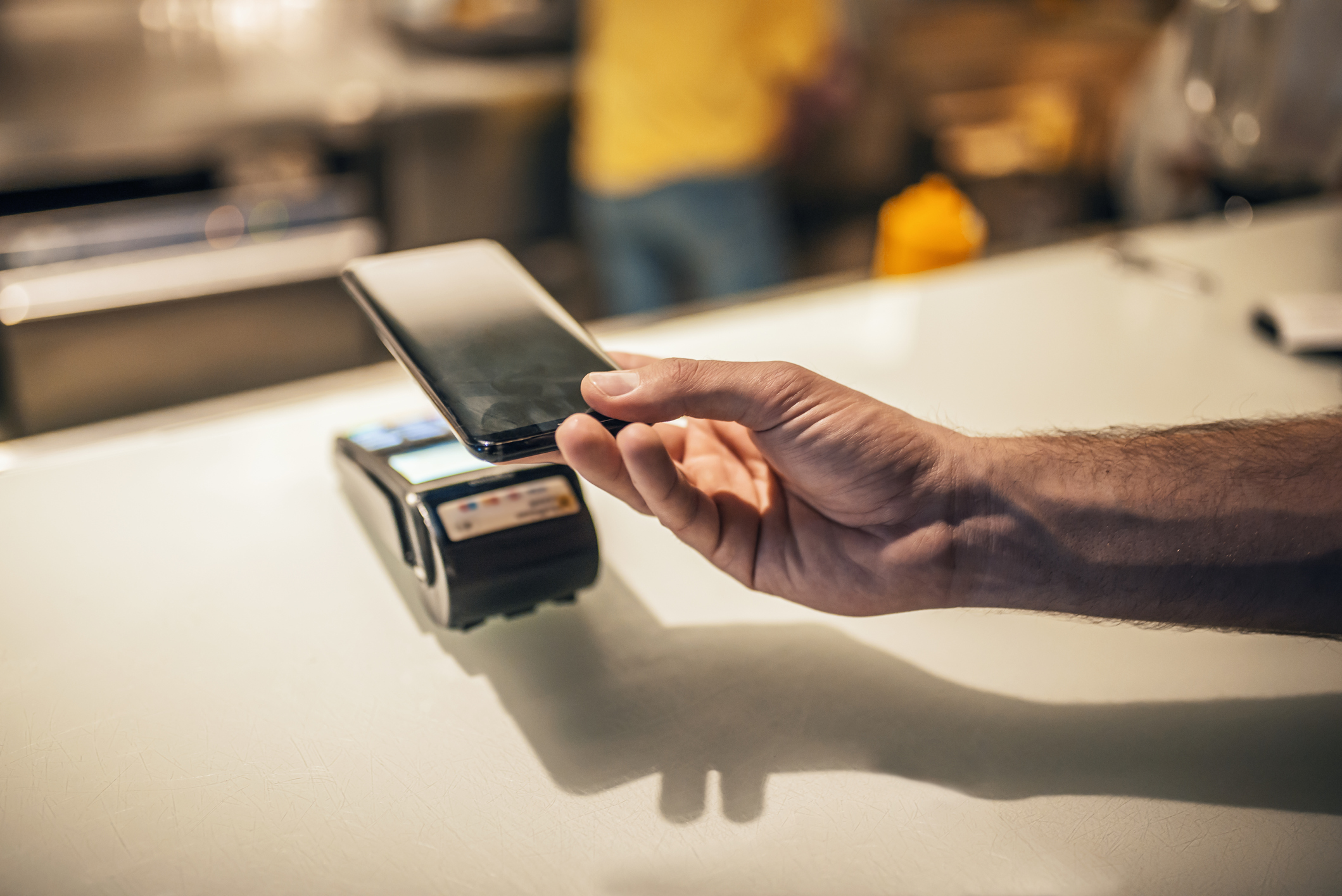 Human hand with smartphone paying for order in cafe with help of swipe system. Contact less payment by phone. Customer paying with NFC technology. Photo of Man paying with NFC technology on mobile phone, in restaurant, bar, cafe.