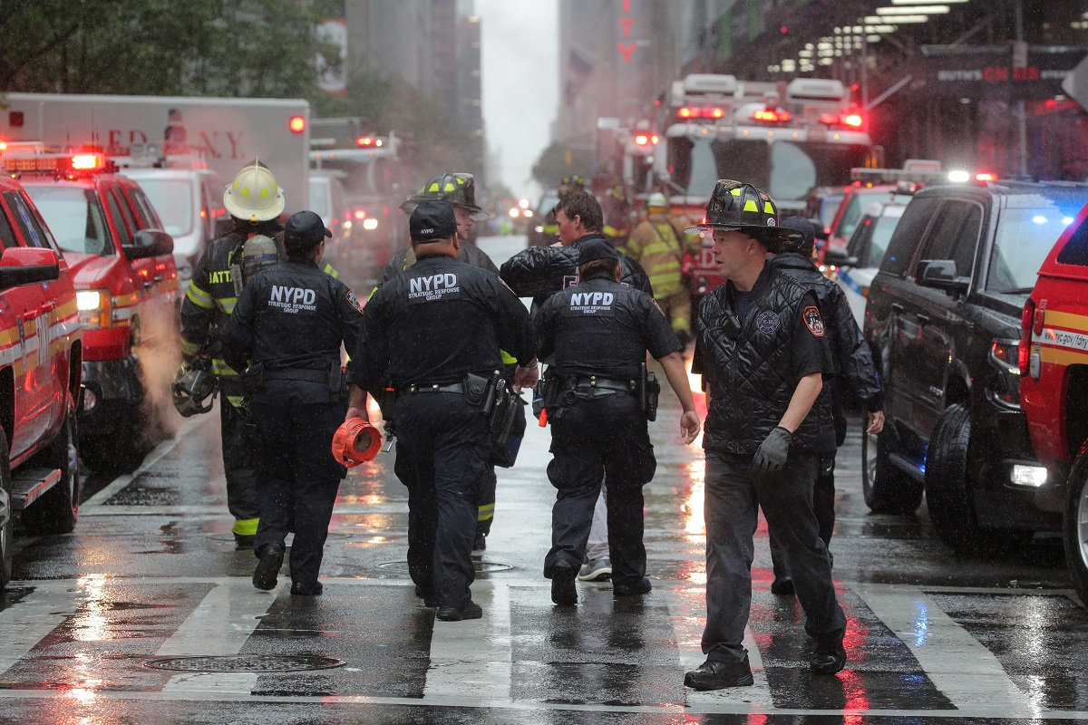 New York City police and firefighters arrive at the scene after a helicopter crashed atop a building in Times Square and caused a fire on the roof in the Manhattan borough of New York, New York, U.S., June 10, 2019. REUTERS/Brendan McDermid