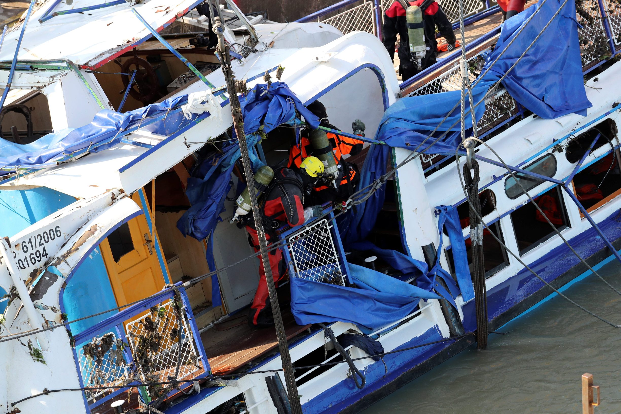 Members of a salvage crew are seen aboard The Mermaid, a Hungarian boat which sank in the Danube river near Margaret bridge, during a salvage operation in Budapest, Hungary, June 11, 2019. REUTERS/Marko Djurica