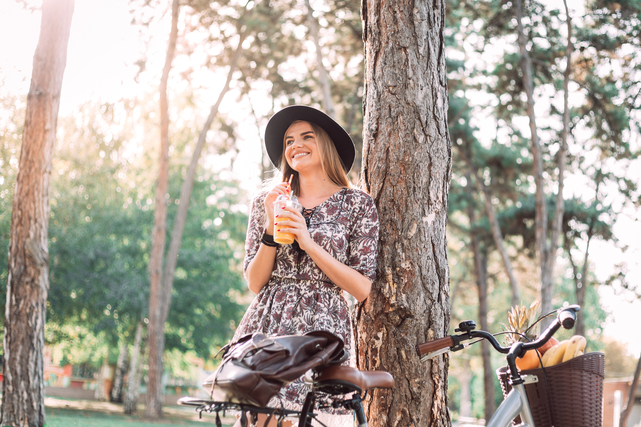 Woman is leaning against a tree while drinking orange juice