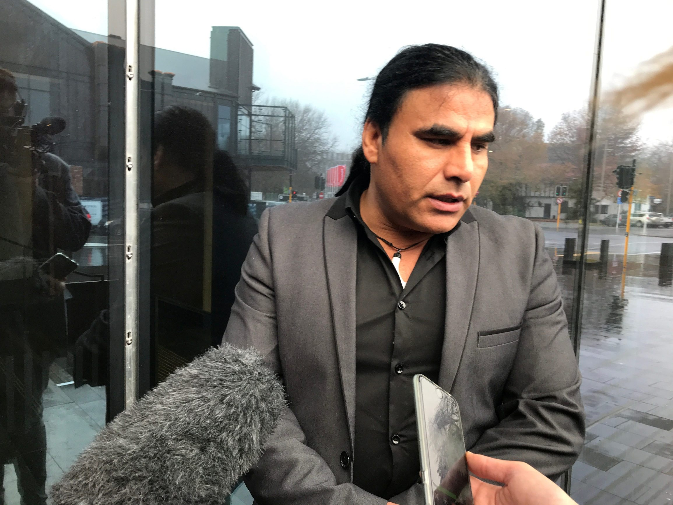 Abdul Aziz, who chased away gunman Brenton Tarrant with an Eftpos machine at Linwood mosque on March 15, speaks to journalists outside the Christchurch High Court in Christchurch, New Zealand June 14, 2019.   REUTERS/Charlotte Greenfield