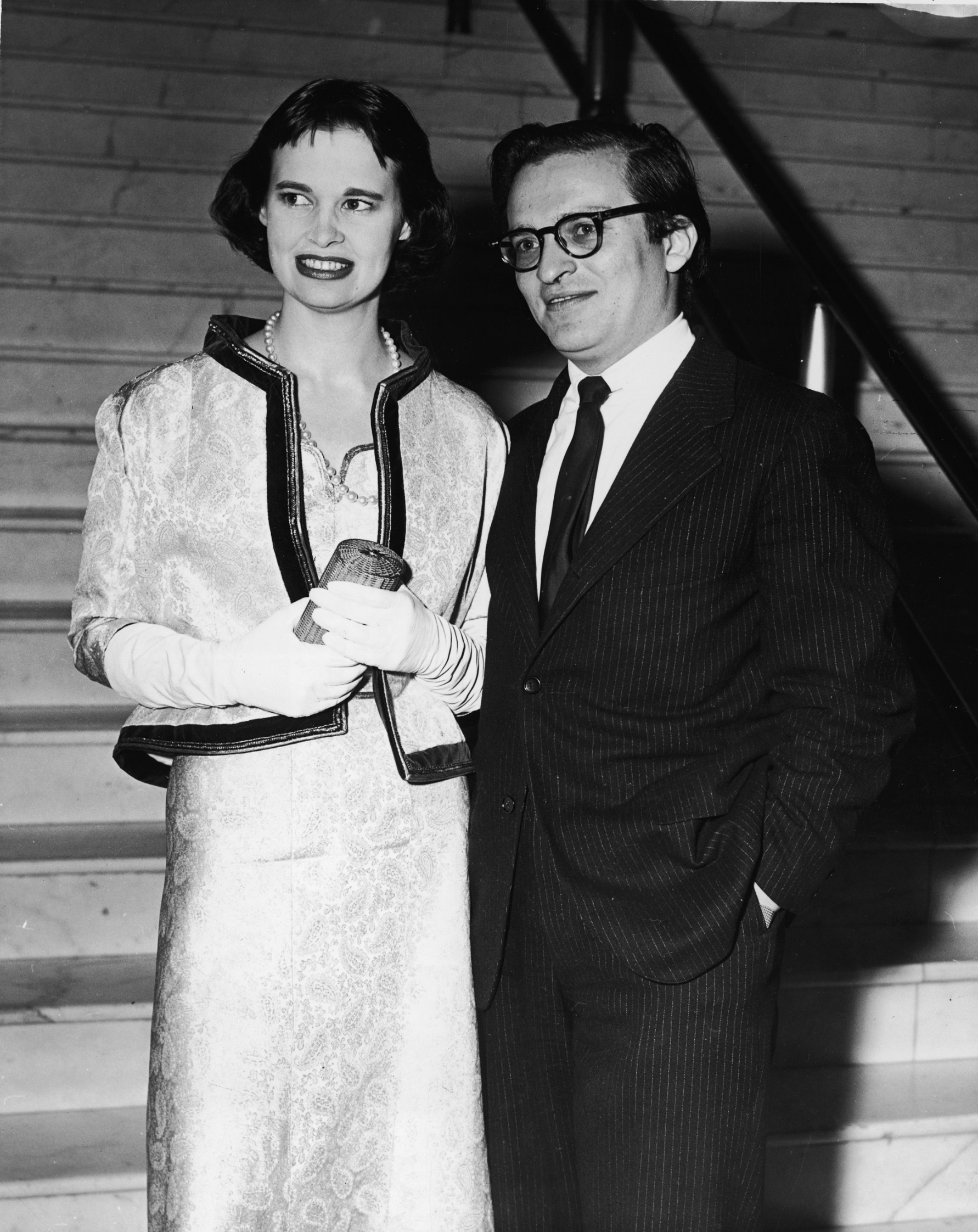 American heiress and designer Gloria Vanderbilt and her second husband American film director Sidney Lumet stand together at the foot of a marble staircase, early 1960s. (Photo by Getty Images)