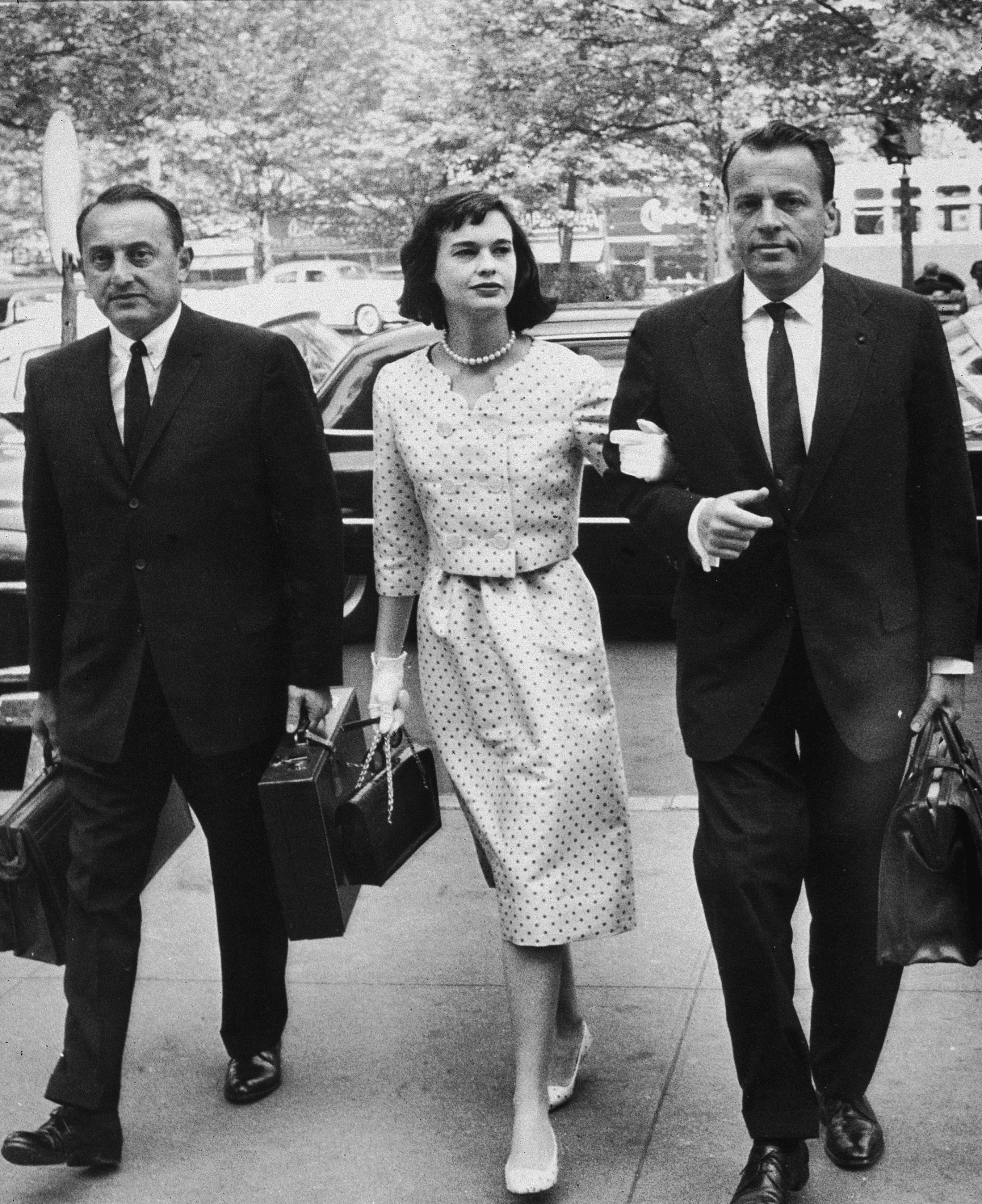 American heiress and socialite Gloria Vanderbilt walks with her attorneys on the way to a custody hearing with her former husband, Leopold Stokowski, June 5, 1959. Vanderbilt wears a polka dot dress with matching jacket and shoes. (Photo by Hulton Archive/Getty Images)