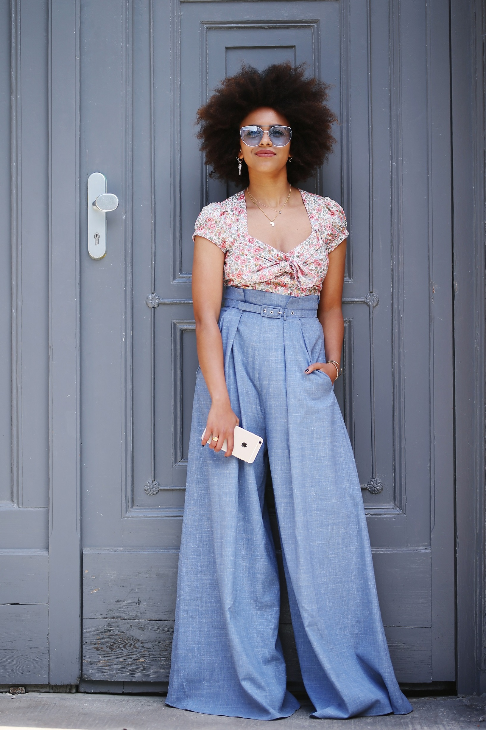 BERLIN, GERMANY - JULY 04: Fashion journalist Aminata Belli, wearing a flower t-shirt, blue sunglasses and denim pants, is seen during the Mercedes-Benz Fashion Week Berlin Spring/Summer 2018 at Kaufhaus Jandorf on July 4, 2017 in Berlin, Germany.  (Photo by Thomas Niedermueller/Getty Images)
