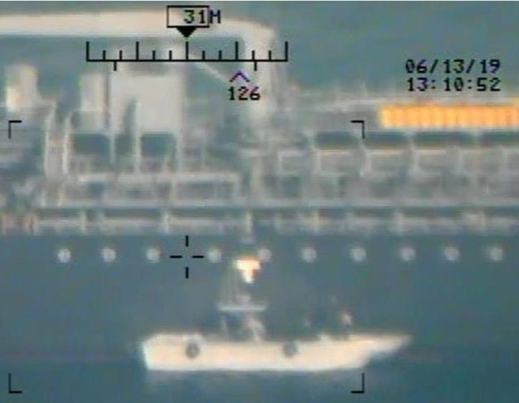 A U.S. military image released by the Pentagon in Washington on June 17, which is says was taken from a U.S. Navy MH-60R helicopter in the Gulf of Oman, shows personnel that the Pentagon says are members of the Islamic Revolutionary Guard Corps Navy removing an unexploded limpet mine from the vessel M/T Kokuka Courageous, a Japanese owned commercial motor tanker, after another mine exploded on the side of the ship, June 13, 2019. Picture taken June 13, 2019.  U.S. Navy/Handout via REUTERS   ATTENTION EDITORS-THIS IMAGE HAS BEEN SUPPLIED BY A THIRD PARTY.