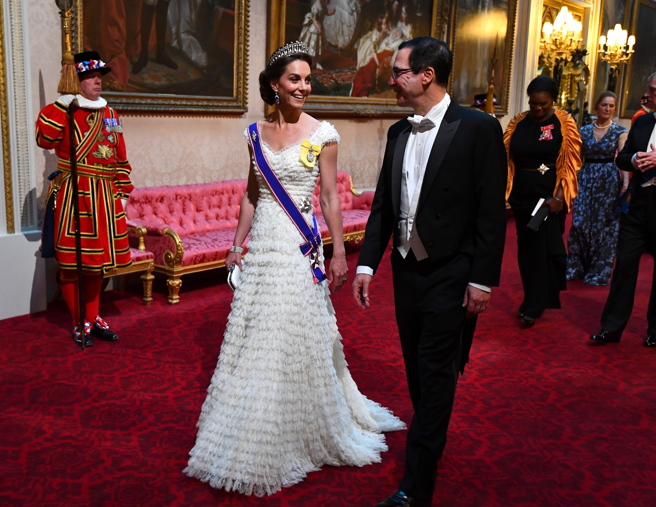 LONDON, ENGLAND - JUNE 03: Catherine,Duchess of Cambridge and United States Secretary of the Treasury, Steven Mnuchin arrive through the East Gallery for a State Banquet at Buckingham Palace on June 3, 2019 in London, England. President Trump's three-day state visit will include lunch with the Queen, and a State Banquet at Buckingham Palace, as well as business meetings with the Prime Minister and the Duke of York, before travelling to Portsmouth to mark the 75th anniversary of the D-Day landings.  (Photo by Victoria Jones- WPA Pool/Getty Images)