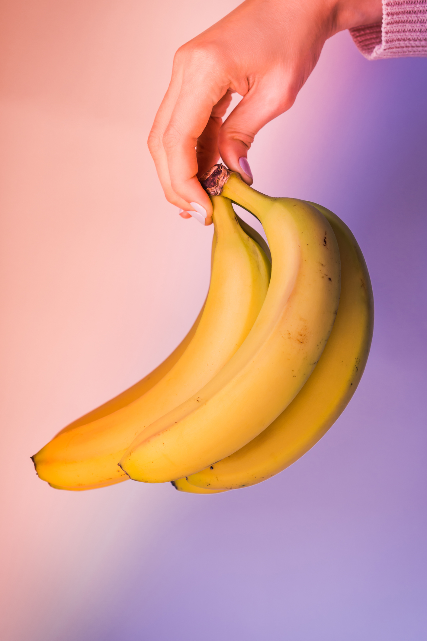 Bunch of fresh bananas in woman's hand on multi color neon background with soft light