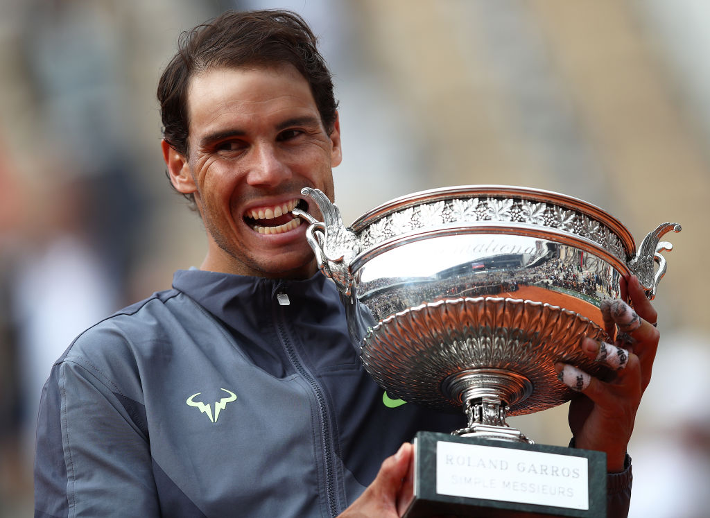 PARIS, FRANCE - JUNE 09: Rafael Nadal of Spain bites the trophy after defeating Dominic Thiem of Austria in the final during Day Fifteen of the 2019 French Open at Roland Garros on June 09, 2019 in Paris, France. (Photo by Julian Finney/Getty Images)
