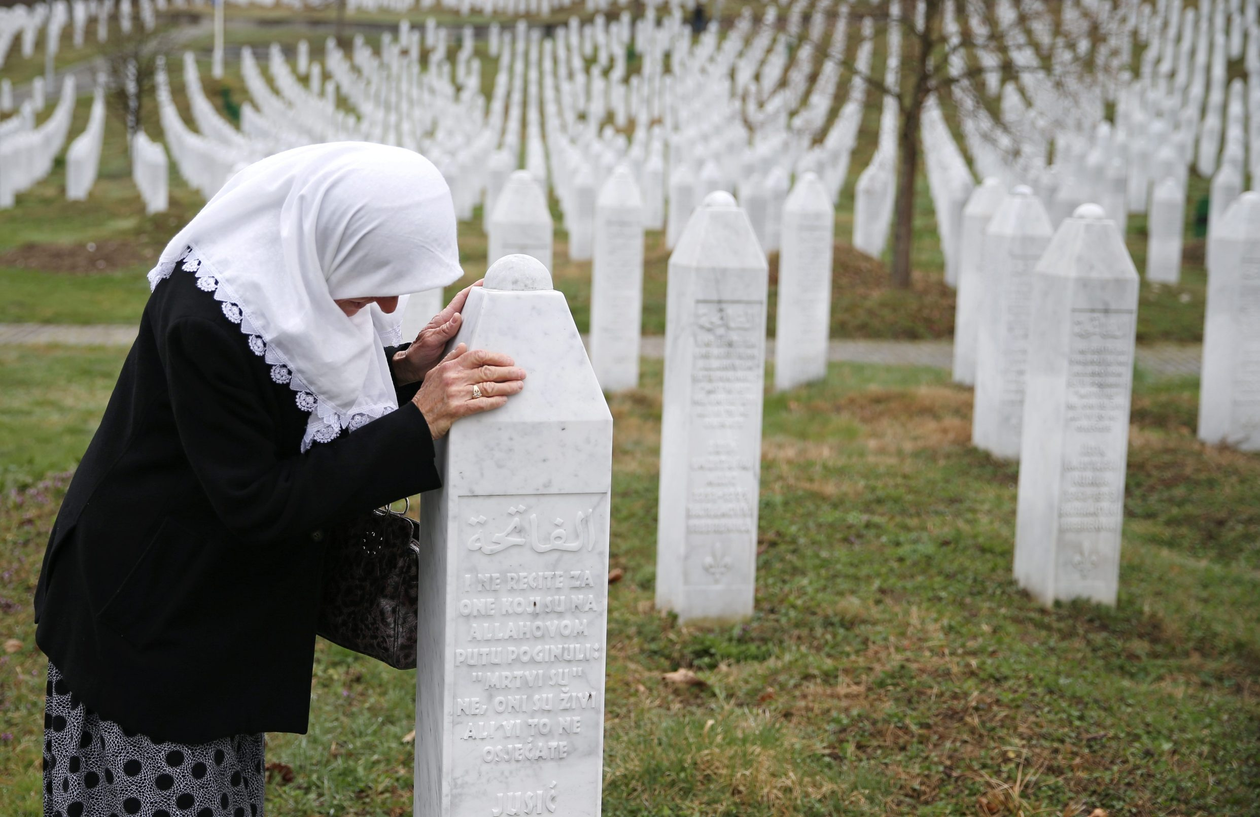 A woman prays near a grave of her family members in the Memorial centre Potocari before the judges verdict on former Bosnian Serb political leader Radovan Karadzic's appeal of his 40 year sentence for war crimes, near Srebrenica, Bosnia and Herzegovina March 20, 2019. REUTERS/Dado Ruvic