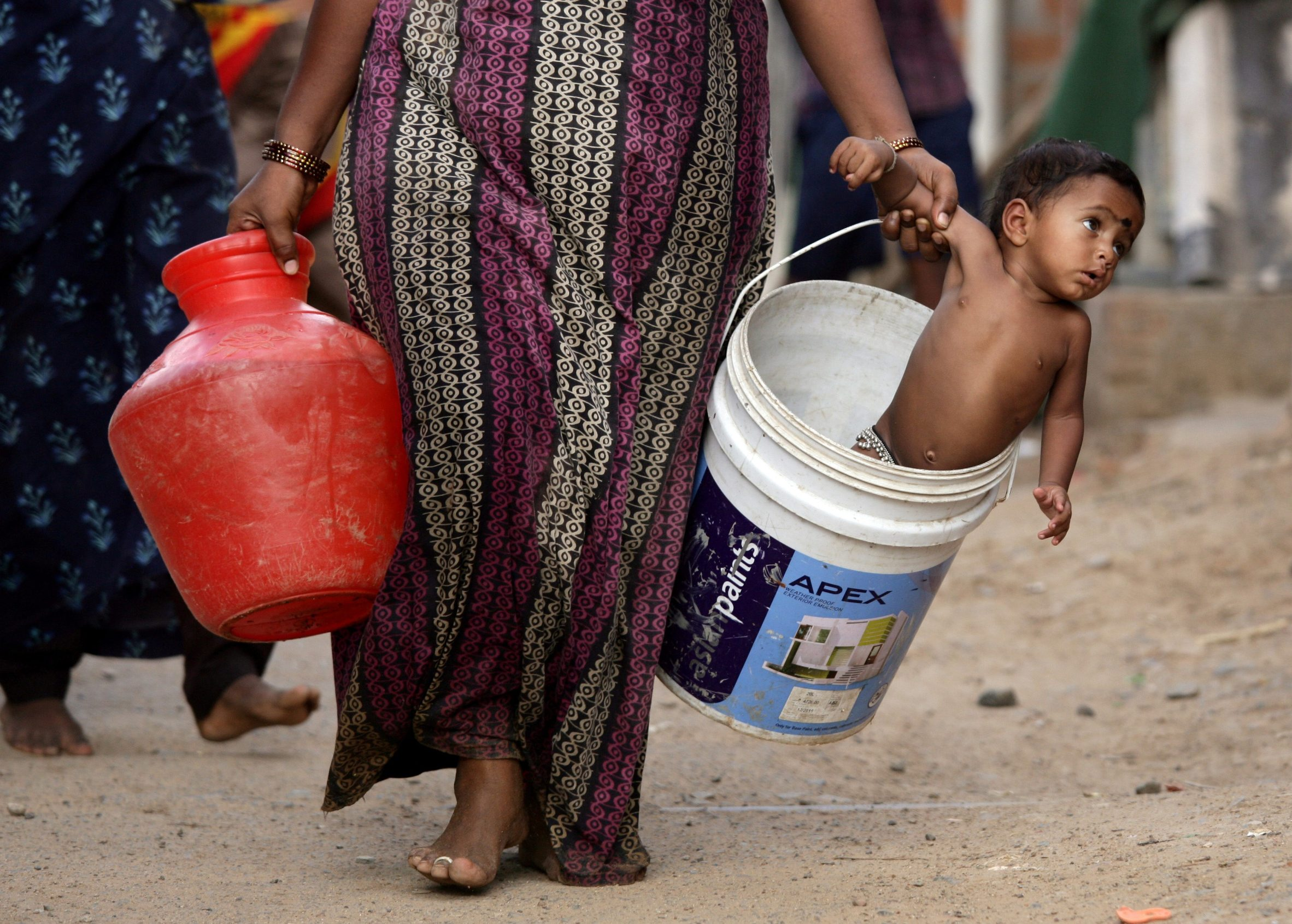 A woman carries her son in a bucket after collecting water from a municipal water tanker on the outskirts of Chennai, India, July 4, 2019. REUTERS/P. Ravikumar     TPX IMAGES OF THE DAY