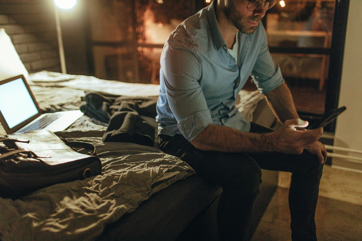 Young man working from a hotel room at night