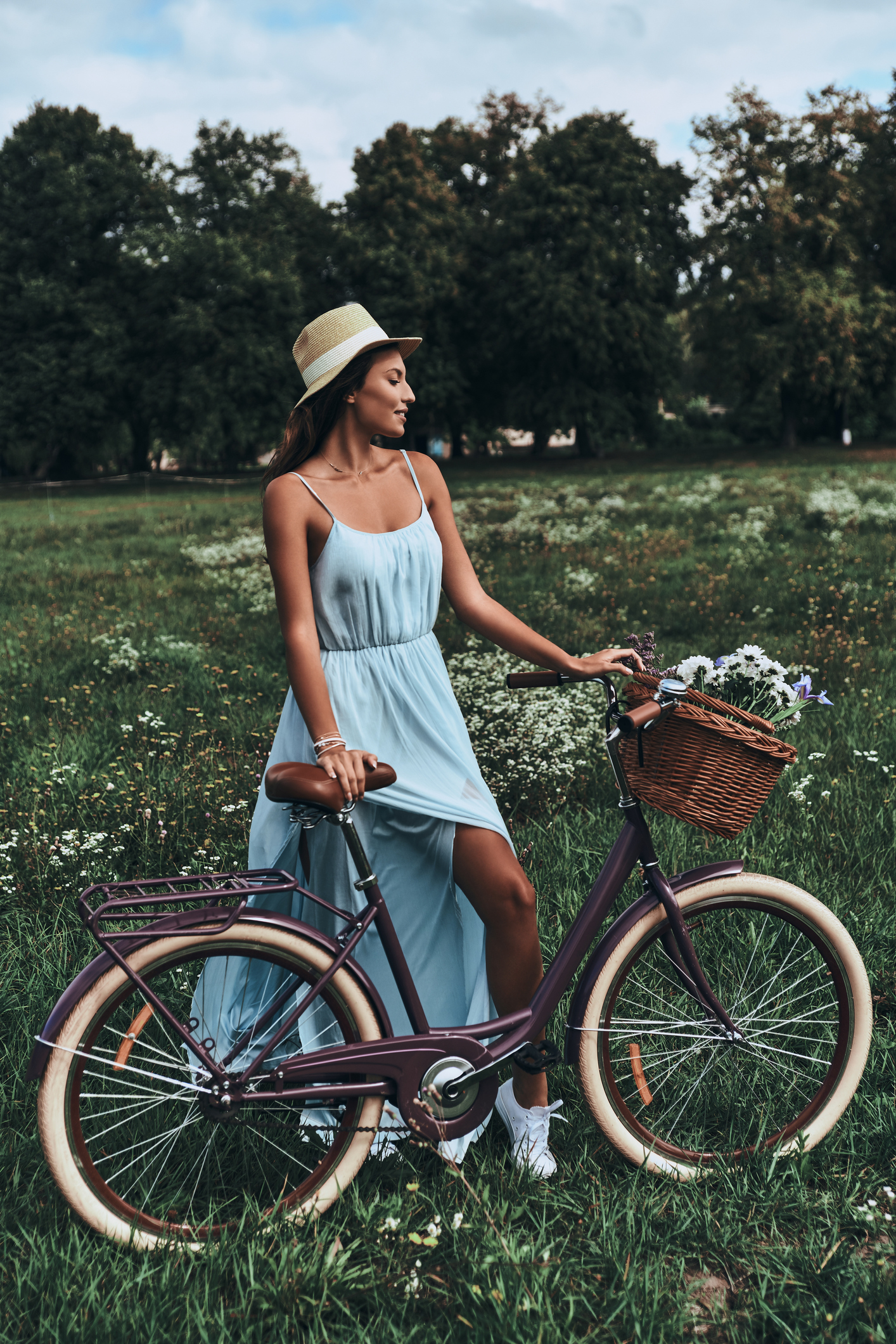 Full length of attractive young woman in dress smiling while standing next to her old fashioned bicycle on the meadow