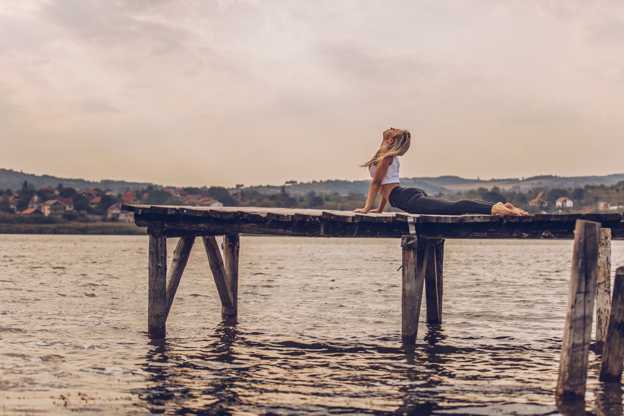 Young woman doing yoga meditation and stretching exercises at the lake jetty