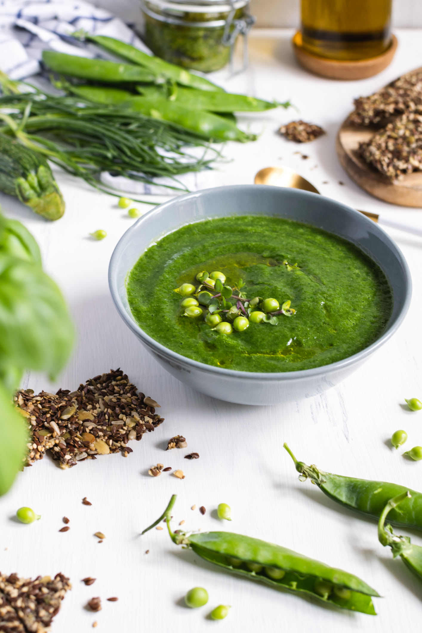 Green peas detox vegetarian soup in gray bowl, white wooden table, seeds crackers - diet food, healthy nutrition, weight loss