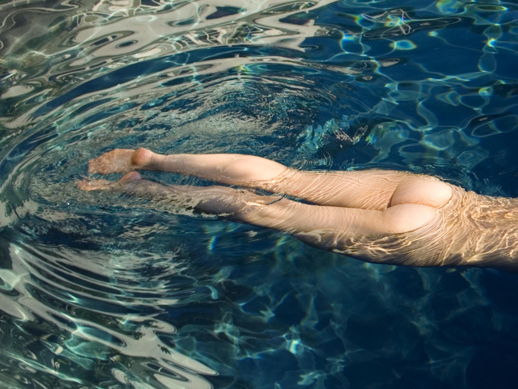 Nude woman floating in pool