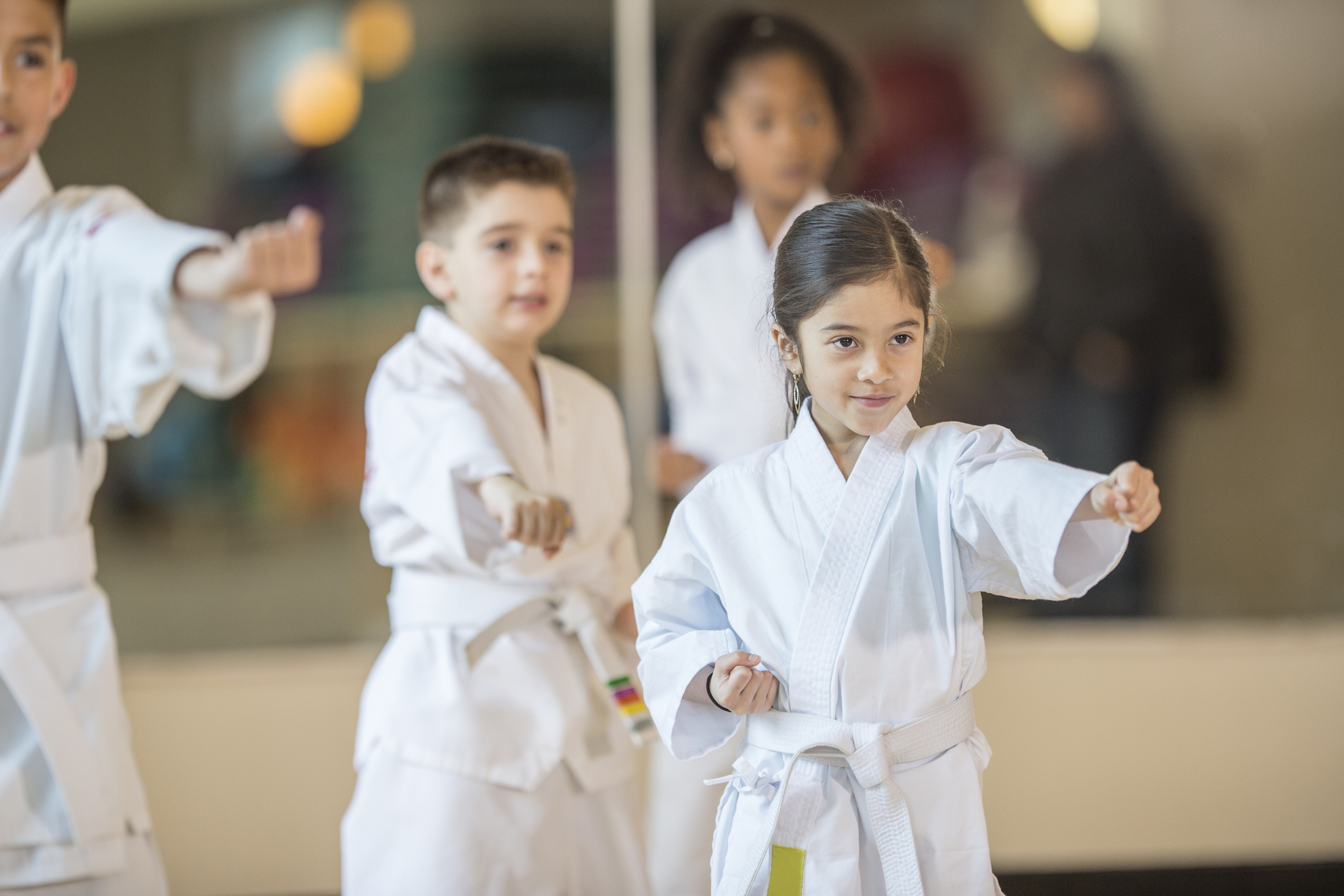 A multi-ethnic group of elementary age children are standing together in formation during their taekwando class.