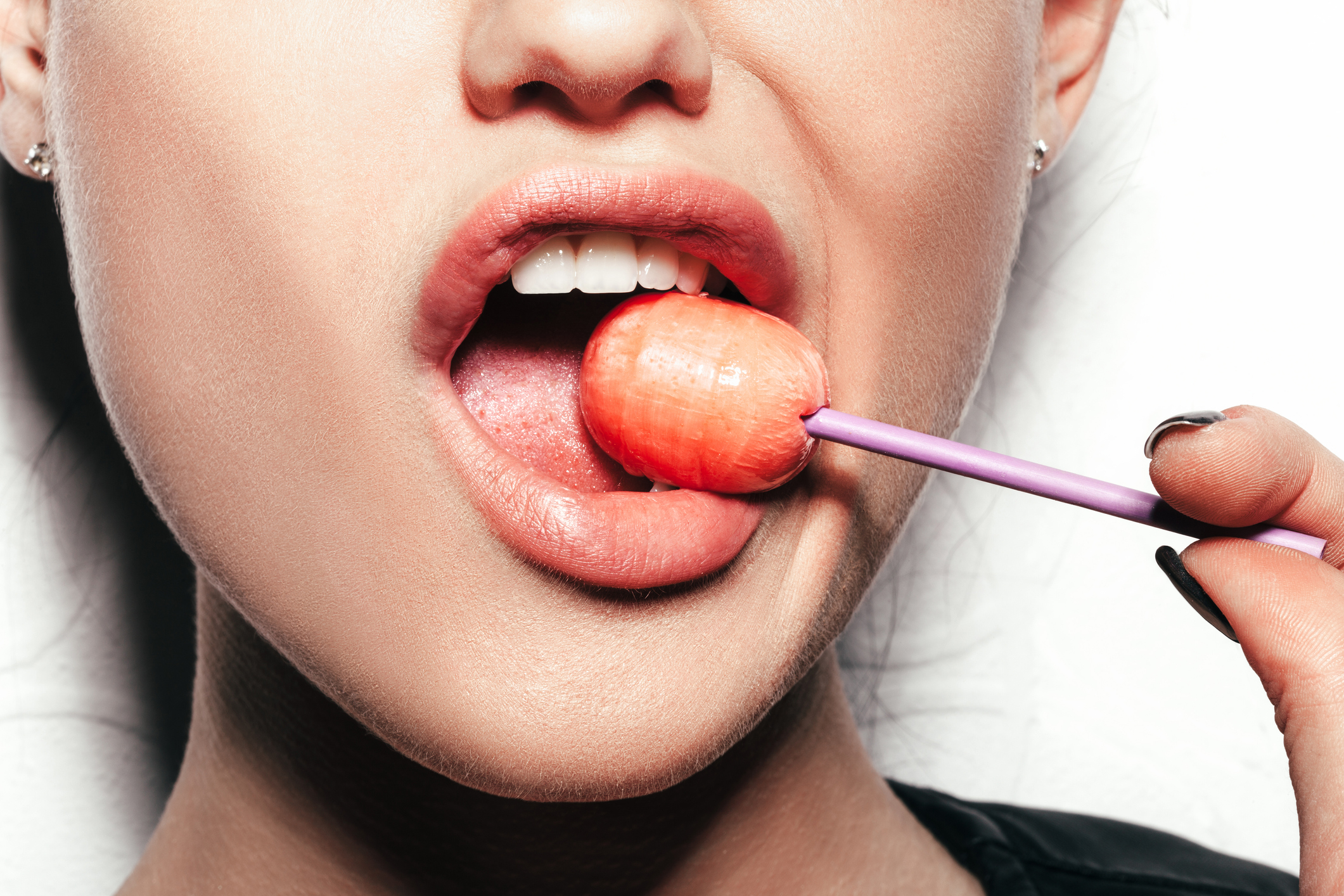 Woman licking a red shiny lollipop. Close up against white background, not isolated