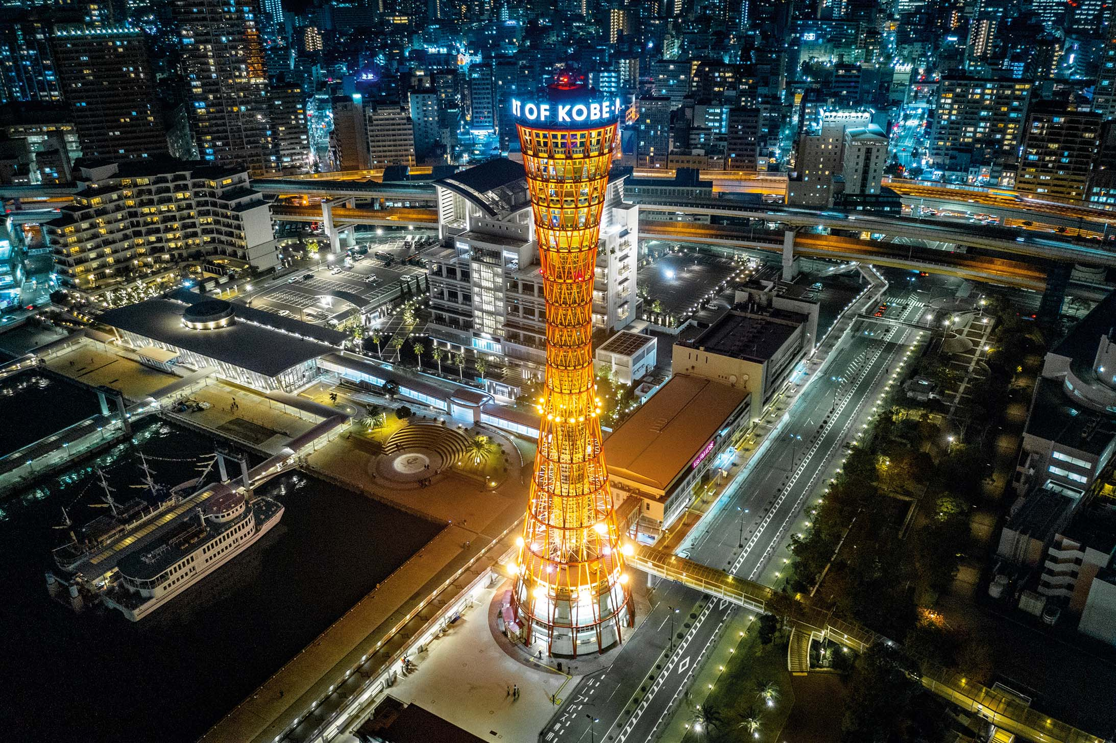 Aerial view down towards the Kobe Port Tower and Kobe Harbor Cityscape. Drone point of view. Nightshot with orange illuminated Kobe Tower. Kobe, Japan, Asia.