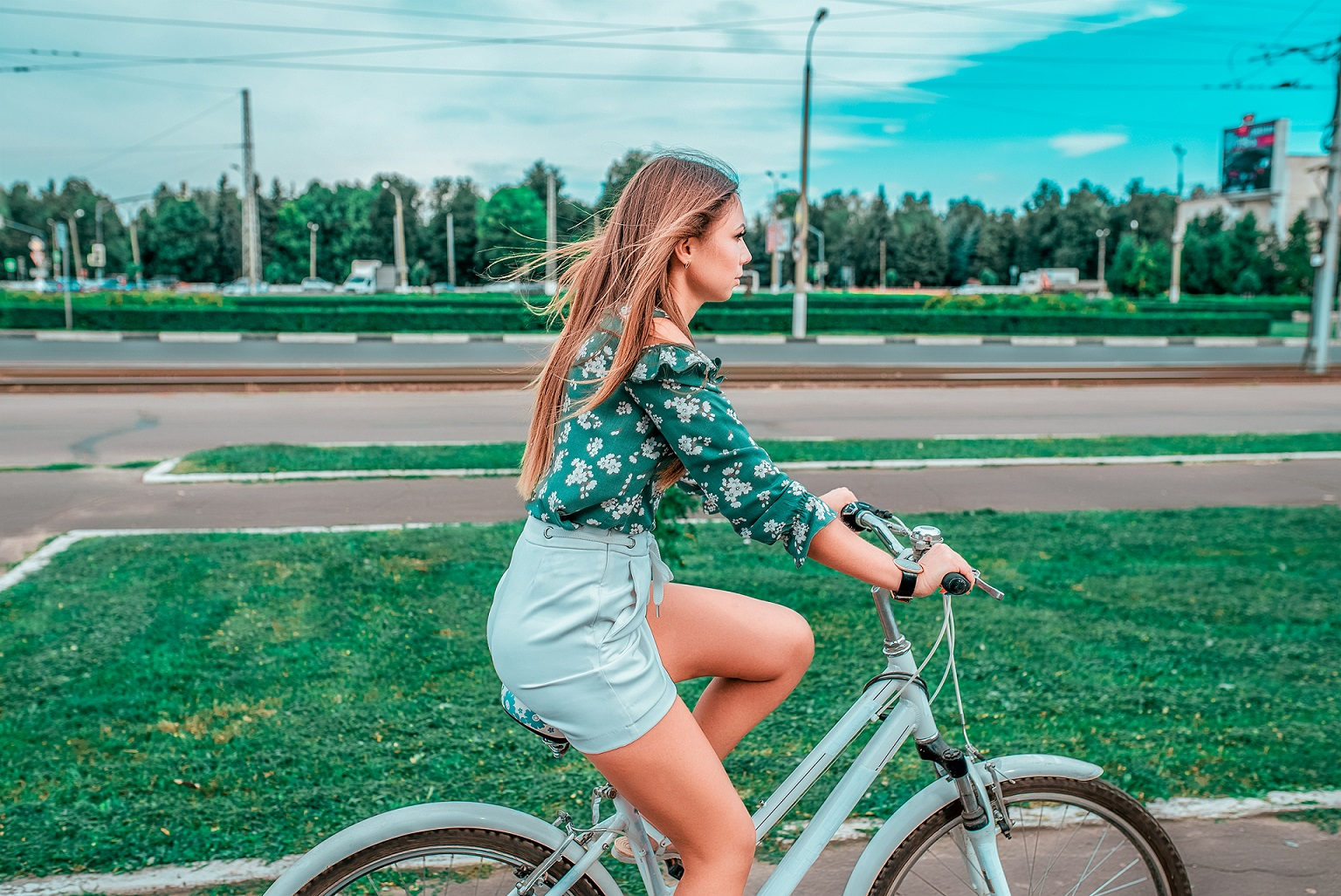 A girl rides a bicycle in the summer in the city on the background of green grass. Returns from a bike run in the weekend in the fresh air, fitness in the city.