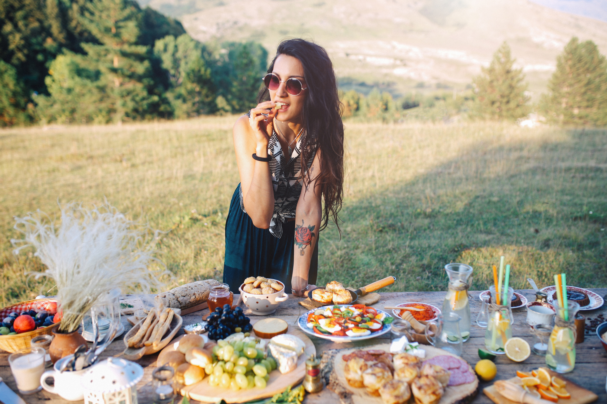 Young woman preparing food for picnic day in the countryside. Various foods on an old, rustic, wooden table.
