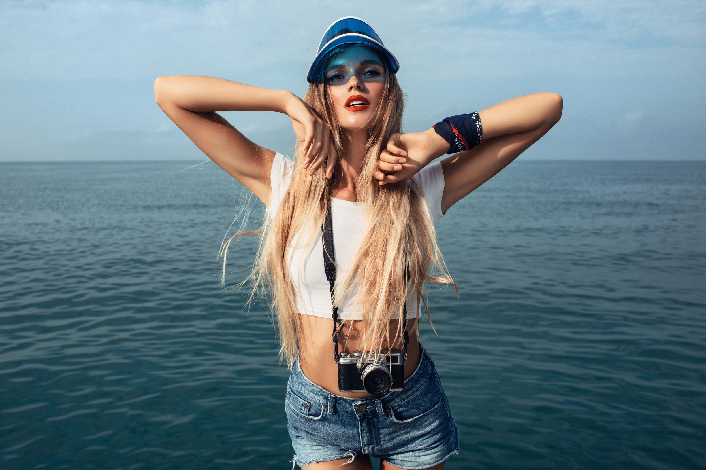 Beautiful woman posing on sea background in blue shorts