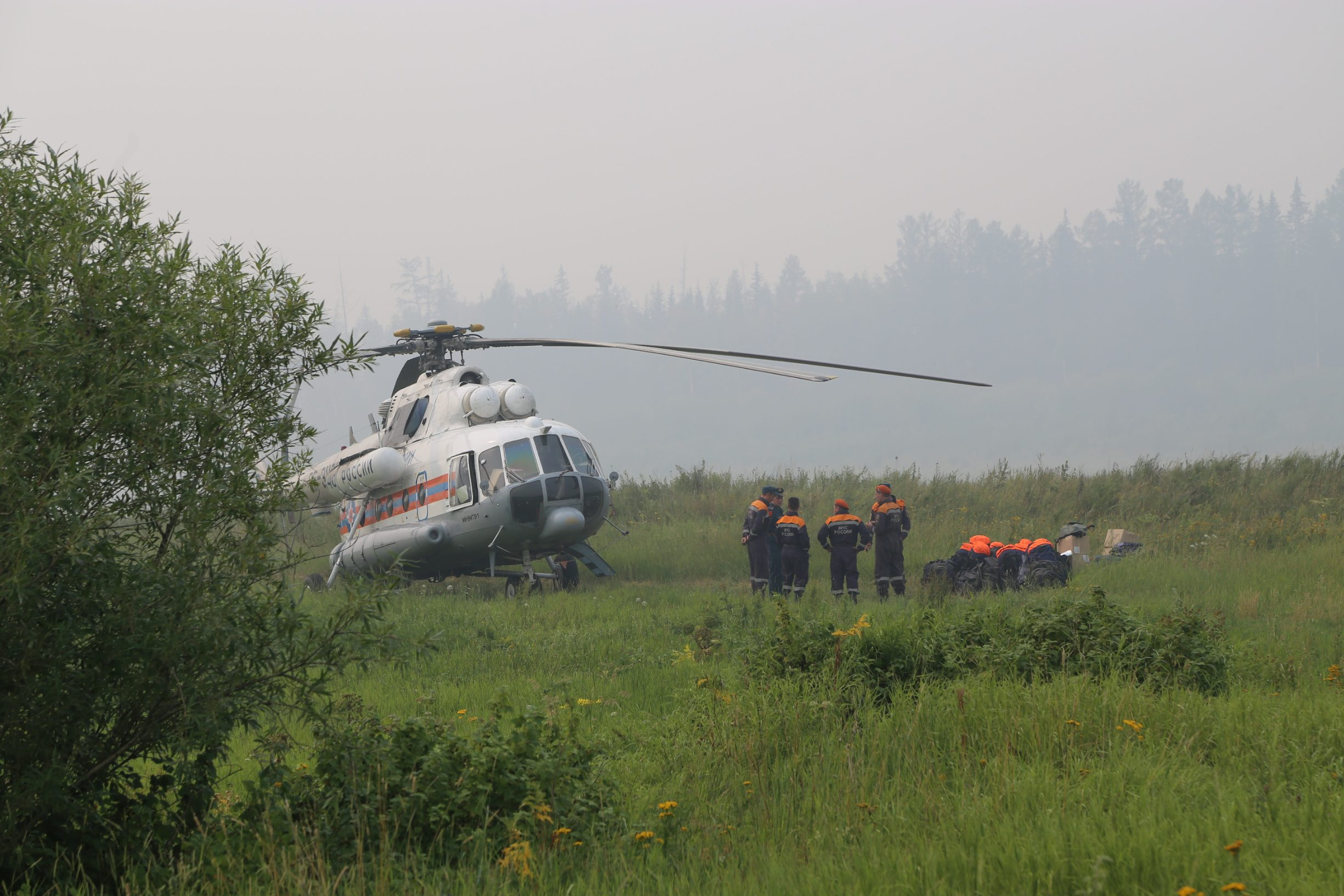 Members of the Russian Emergencies Ministry stand next to a helicopter near the site of a wildfire in Krasnoyarsk region, Russiain this handout picture obtained by Reuters on August 1, 2019. Russian Emergencies Ministry in Krasnoyarsk region/Handout via REUTERS ATTENTION EDITORS - THIS IMAGE WAS PROVIDED BY A THIRD PARTY. NO RESALES. NO ARCHIVES. MANDATORY CREDIT.