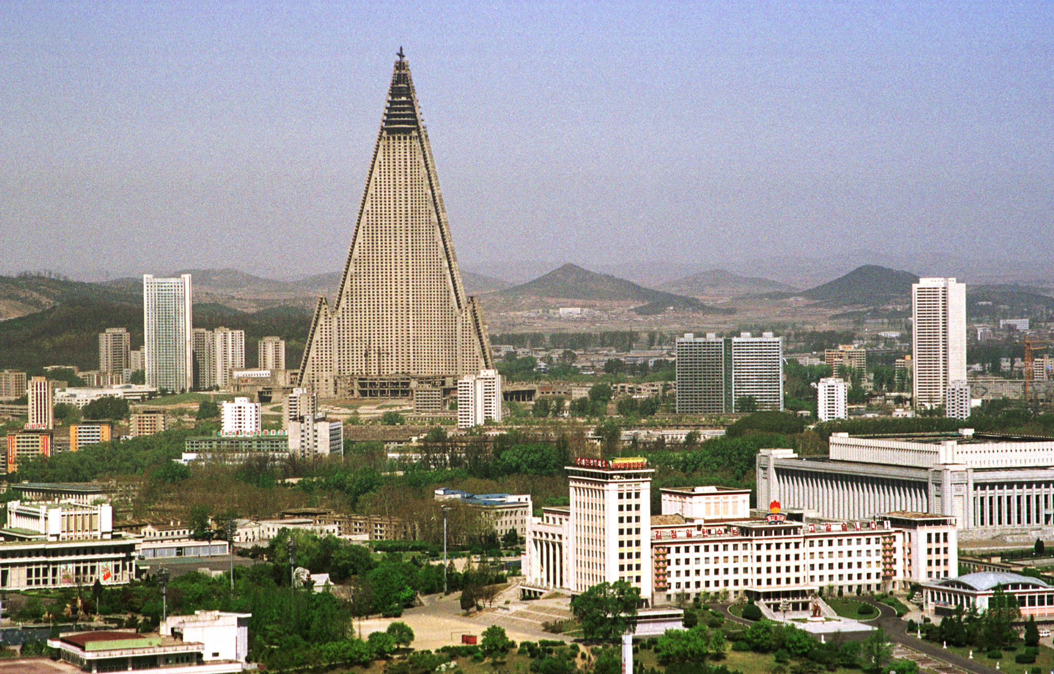 The 105-storey Ryugyong Hotel splits the sky over Pyongyang, the North Korean capital. The picture of a crane sitting idle on top of the hotel has become a familiar one for locals, unchanged for over a decade. The partially complete building now stands tall, but without windows or visitors. Picture taken April 24, 2002. REUTERS/Teruaki Ueno TO ACCOMPANY FEATURE STORY KOREA-NORTH-ECONOMY  ES/RCS - RP3DRICANDAA