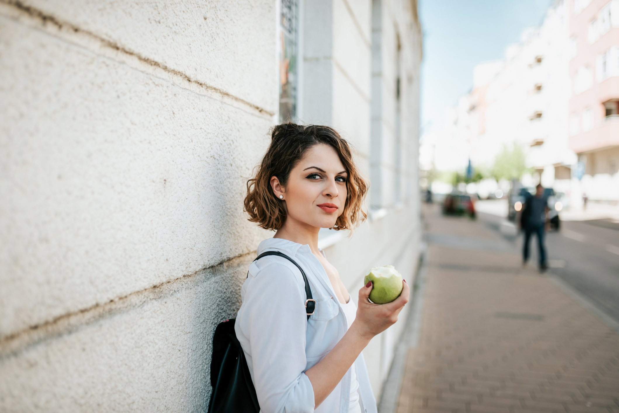 Gorgeous looking woman eating apple on street.