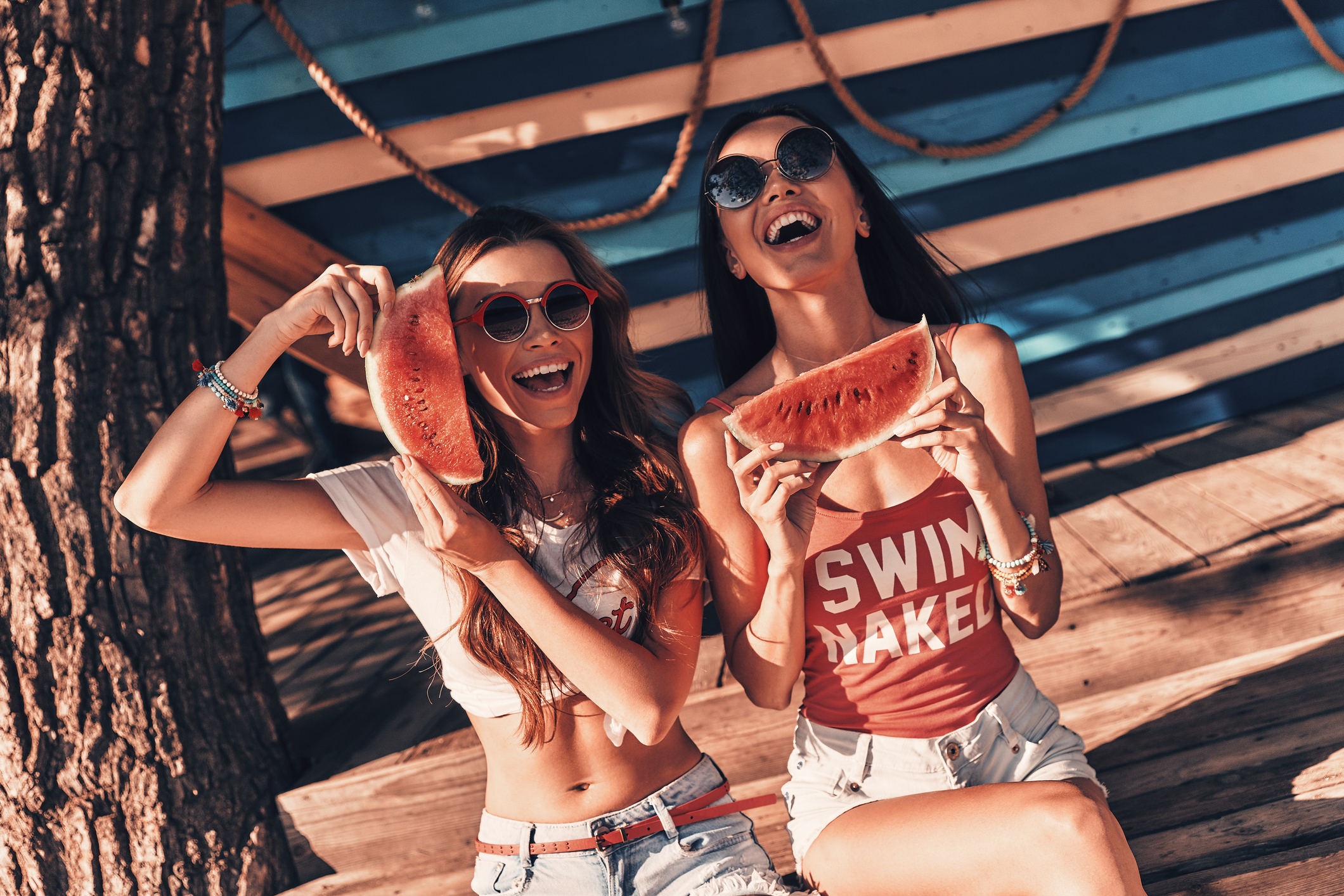 Top view of two attractive young women smiling and eating watermelon while sitting outdoors