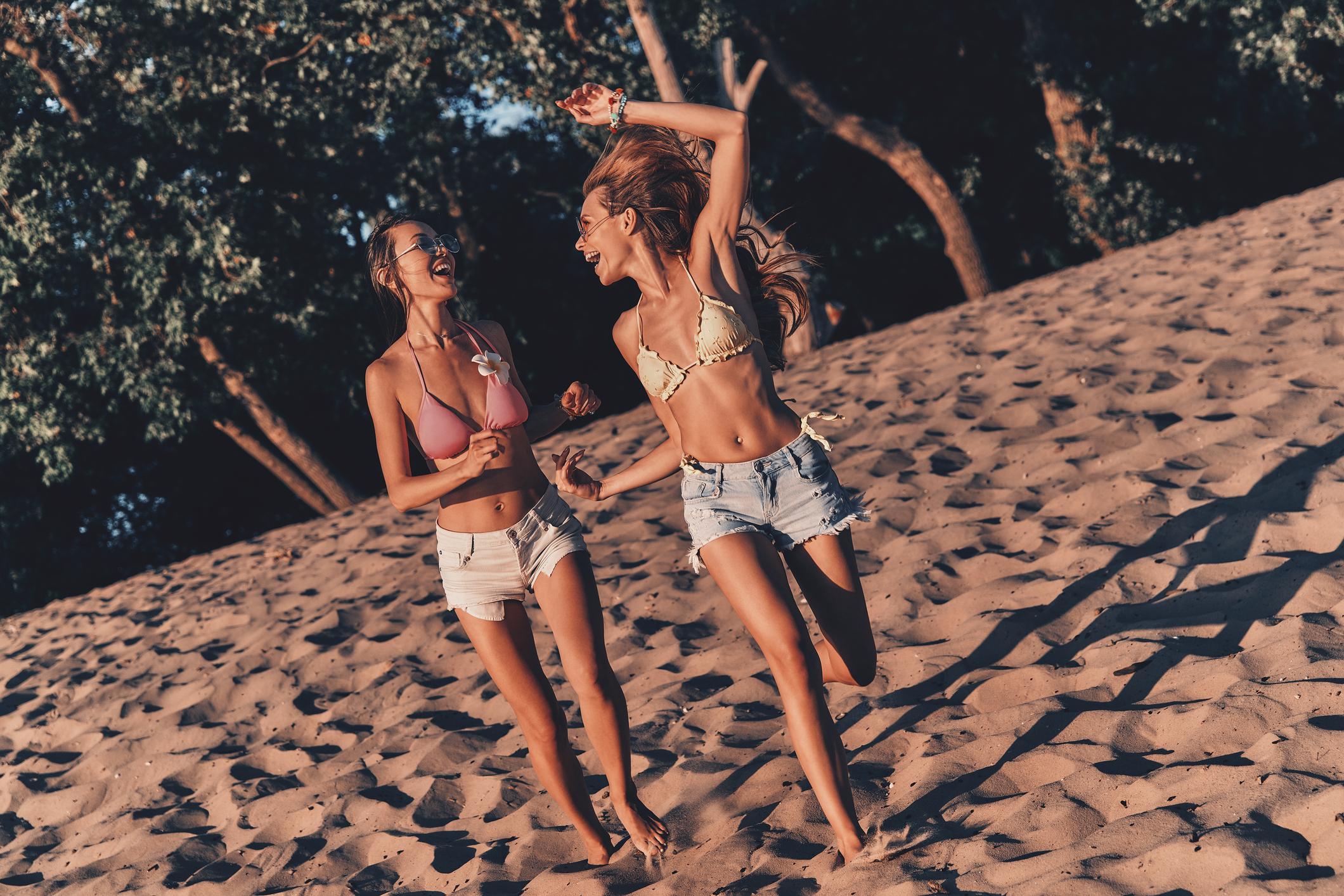 Full length of two attractive young women in shorts and swimwear smiling while running on the beach