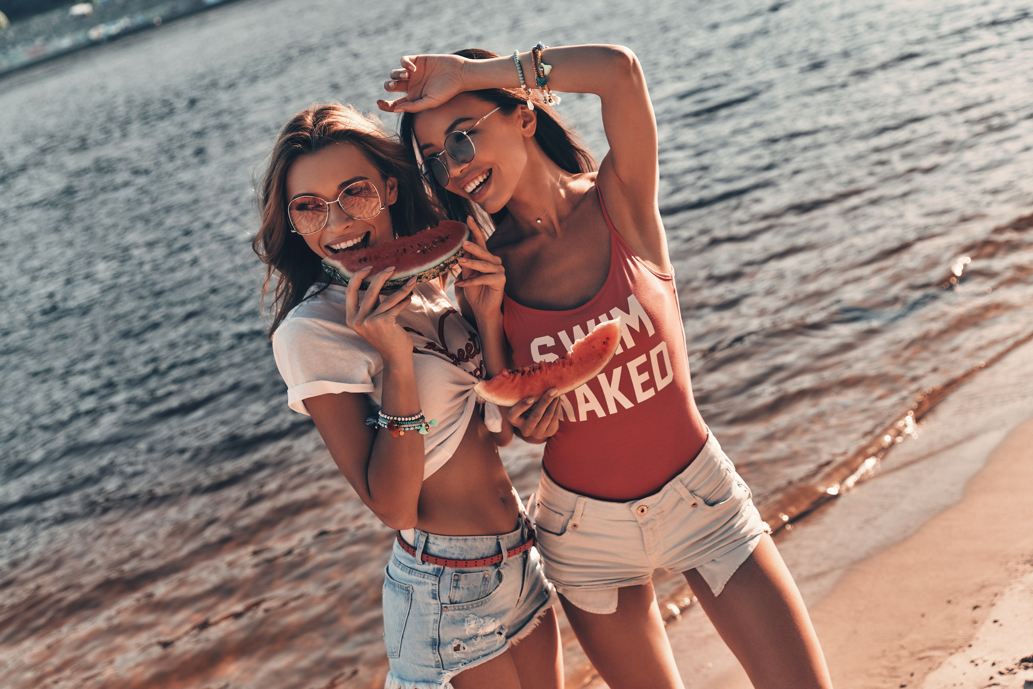 Top view of attractive young women smiling and eating watermelon while standing near the river