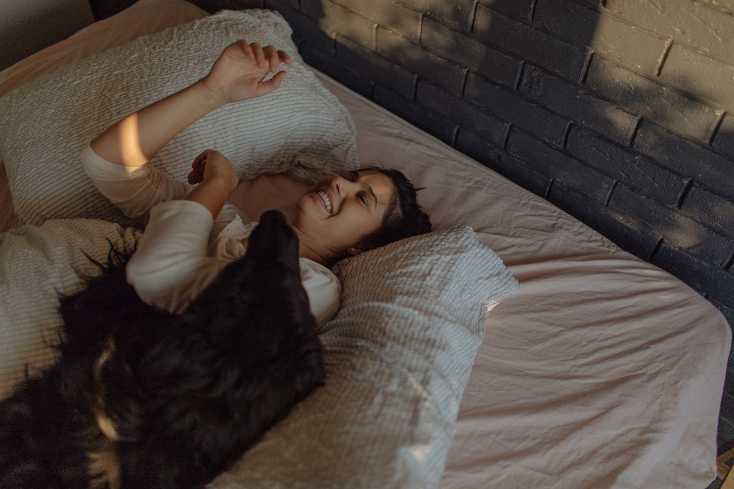 Portrait of a young beautiful woman waking up with her dog