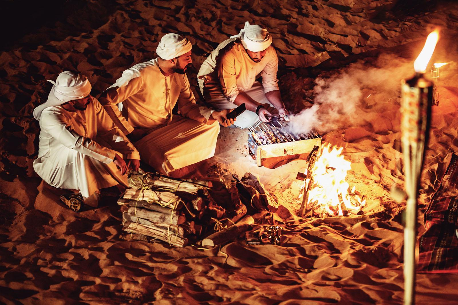 Brotherhood, Friends, Arabs, Dubai - Arab Friends Seated Around the Bonfire at a Desert Camp and Enjoying a Casual Conversation