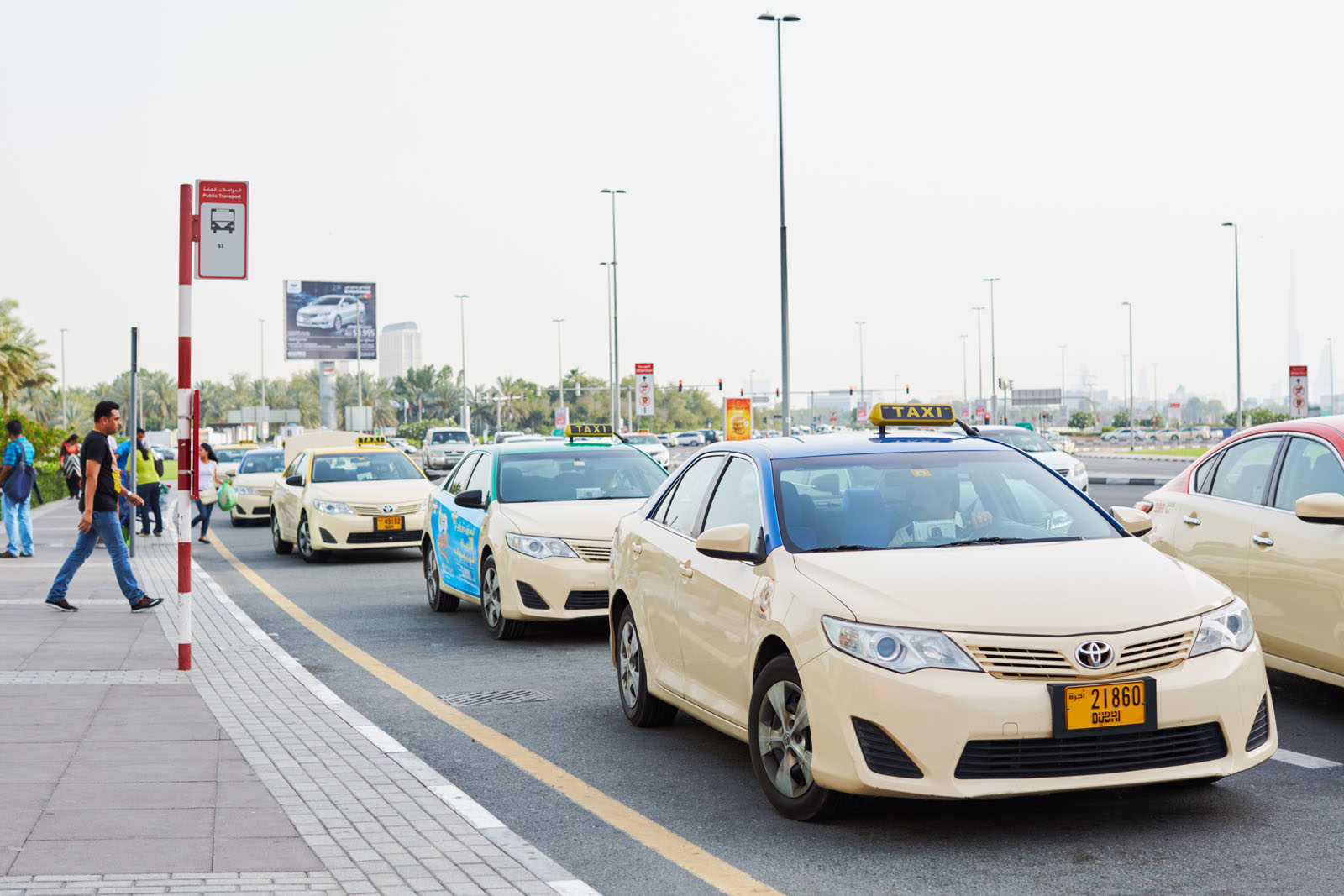 Dubai, United Arab Emirates - May 6, 2016: Blue and red top taxis at Deira City Centre.The Cars Taxis Corporation operates cream-coloured blue roof taxis and Dubai Taxi Corporation operates cream-coloured red roof taxis.The meter generally begins as Dhs. 12.00 when a requesting a cab from the call center, and 5.00 Dhs. when taking a taxi on the road and is generally charged by distance at 1.5 Dhs./km. There are approximately 7900 taxis located in the city.