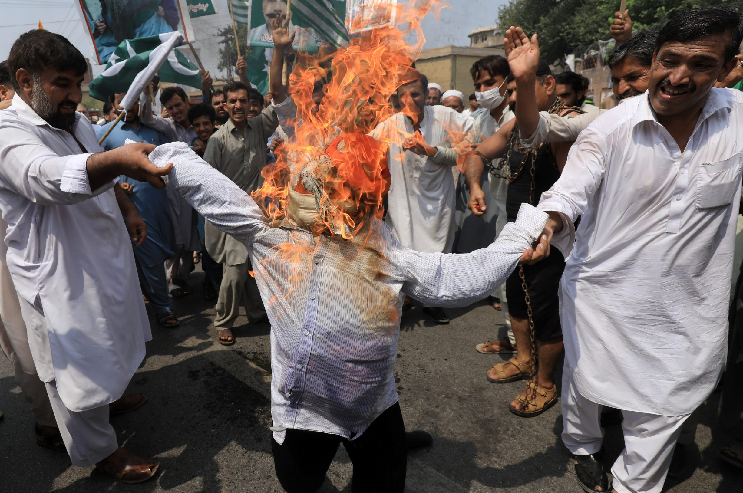 People set on fire an effigy of Indian Prime Minister Narendra Modi, during a countrywide 'Kashmir Hour' demonstration to express solidarity with the people of Kashmir, observing a call by Prime Minister Imran Khan in Peshawar, Pakistan August 30, 2019. REUTERS/Fayaz Aziz