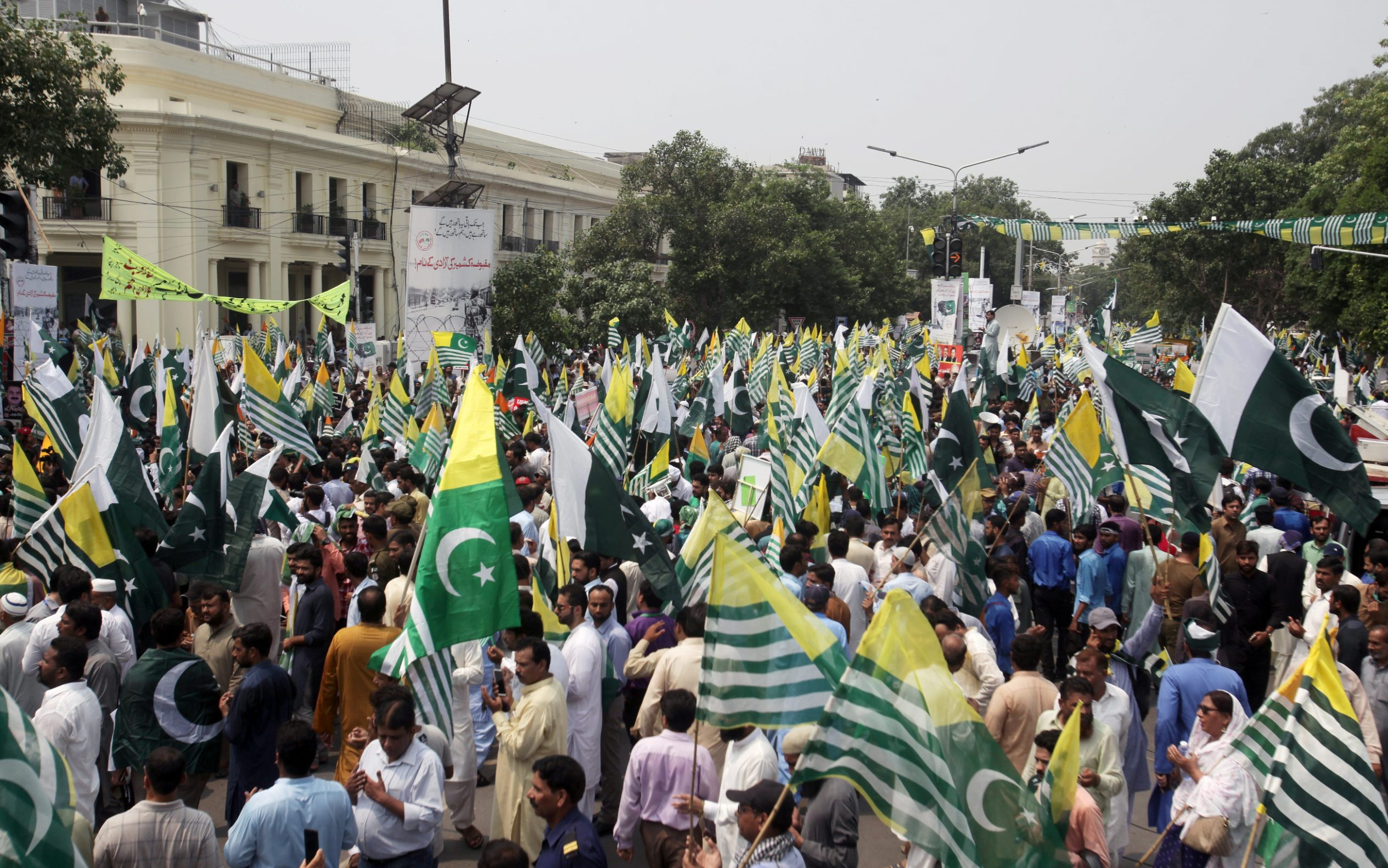 People carrying flags of Pakistan and Azad Kashmir, pray during a countrywide 'Kashmir Hour' demonstration to express solidarity with the people of Kashmir, observing a call by Prime Minister Imran Khan in Lahore, Pakistan August 30, 2019. REUTERS/Mohsin Raza