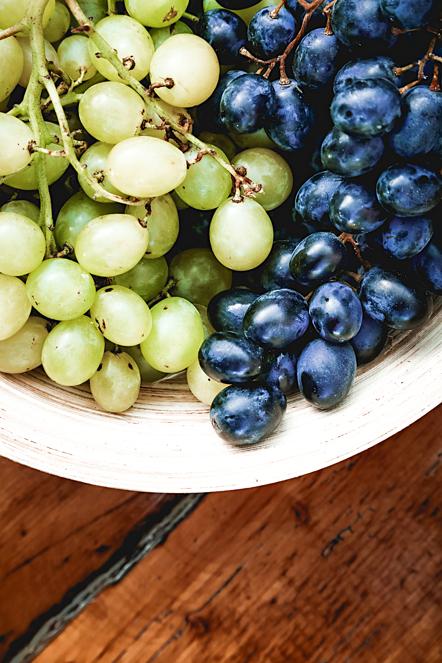 Fresh organic grapes in wooden bowl on rustic wooden table